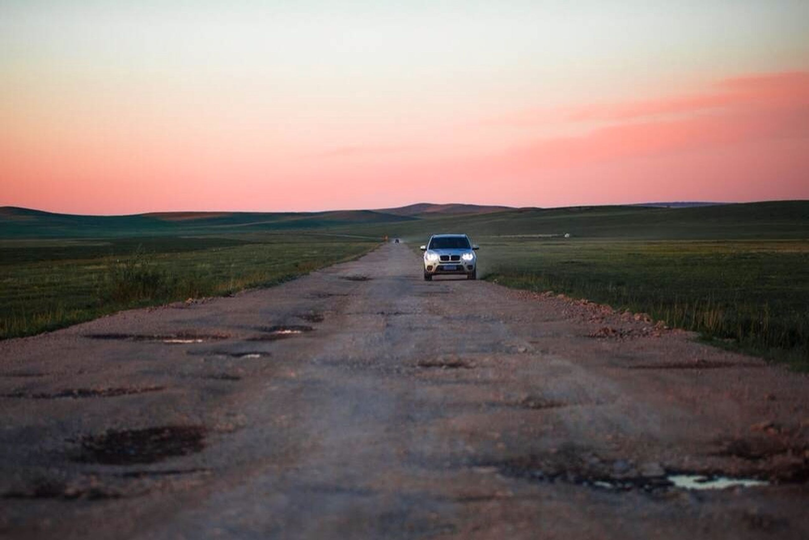 transportation, landscape, sunset, land vehicle, the way forward, mode of transport, field, sky, dirt road, rural scene, road, country road, tranquil scene, diminishing perspective, agriculture, nature, on the move, tranquility