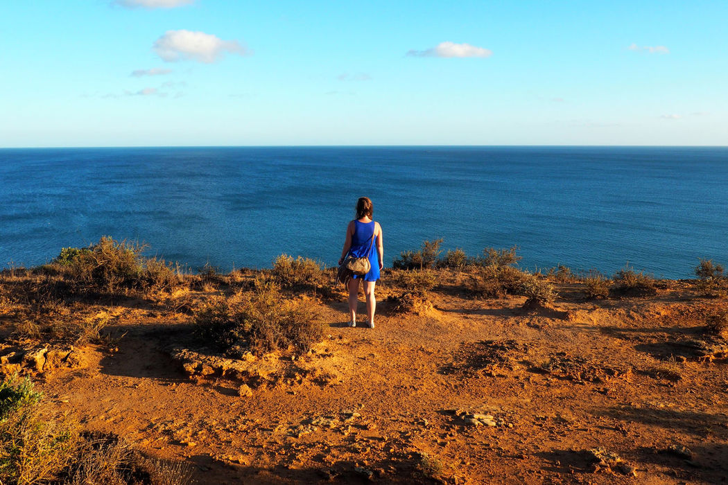 Adventure Alone Blue Dress Casual Clothing Contrast Courage Future Girl Girl Power Goals Horizon Over Water Ocean View Rear View Red Sand Scenics Sea Standing The Way Forward Tourist Travel Vacations Woman TakeoverContrast