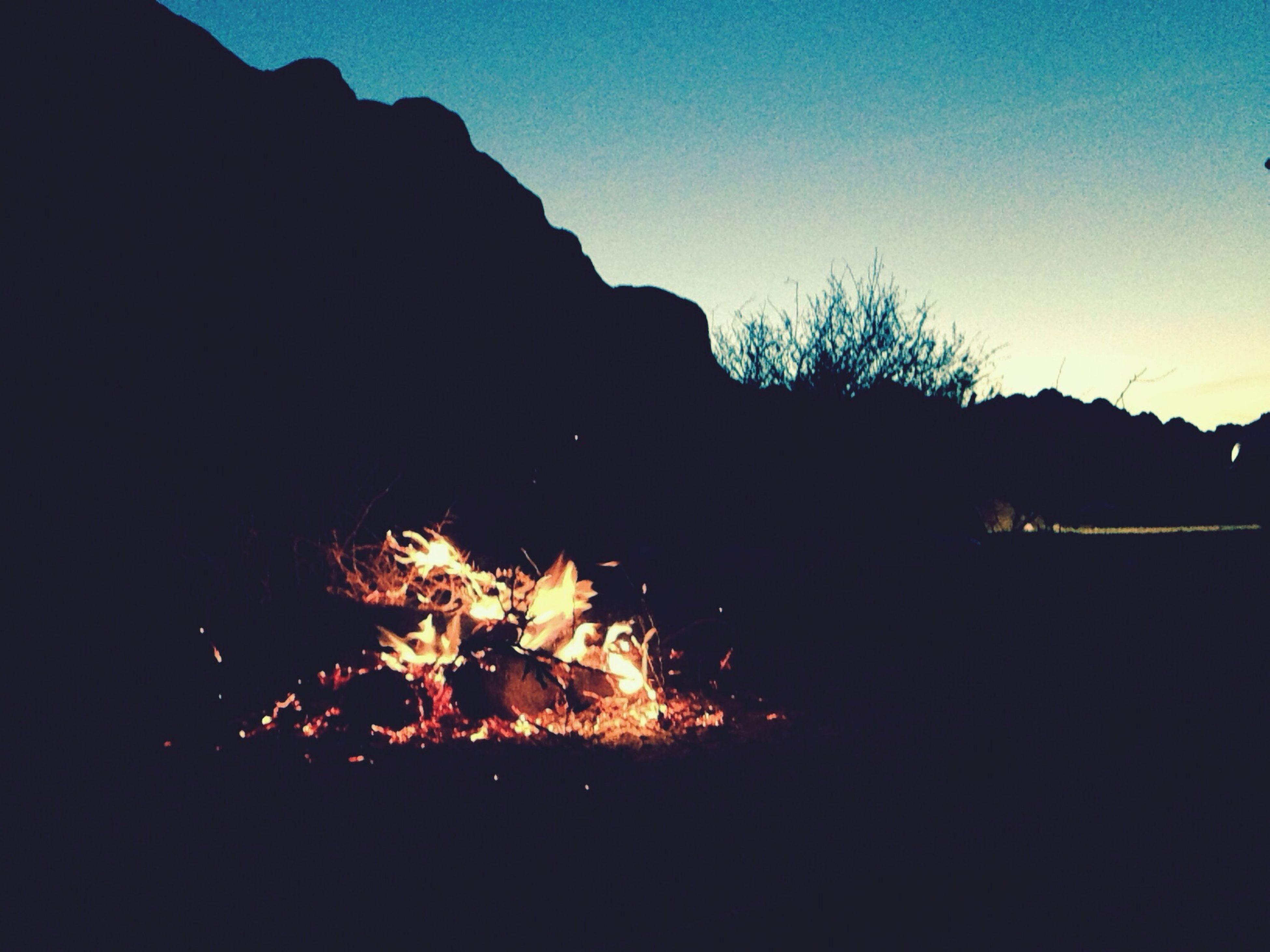 night, silhouette, sky, clear sky, tree, illuminated, dark, copy space, glowing, fire - natural phenomenon, nature, tranquility, outdoors, scenics, tranquil scene, beauty in nature, burning, mountain, no people, low angle view