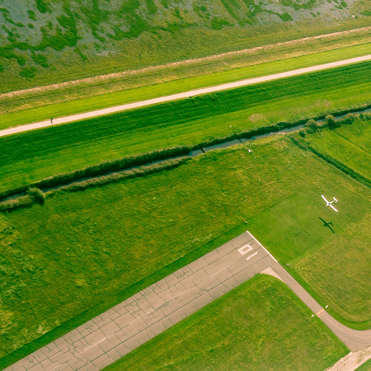 aerial view, agriculture, field, farm, landscape, rural scene, patchwork landscape, scenics, high angle view, green color, airplane, flying, nature, outdoors, tranquil scene, grass, beauty in nature, day, no people, sports track