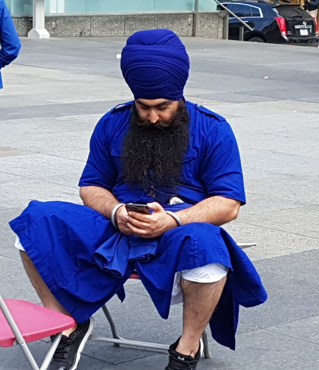 sitting, street, real people, one person, full length, front view, looking down, outdoors, road, day, holding, sidewalk, lifestyles, young adult, adult, people