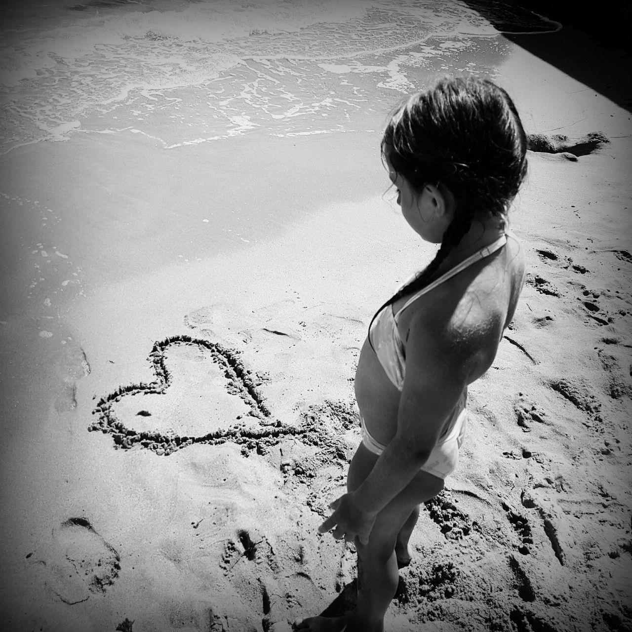 High Angle View Of Girl In Bikini Standing By Heart Shape At Beach During Sunny Day