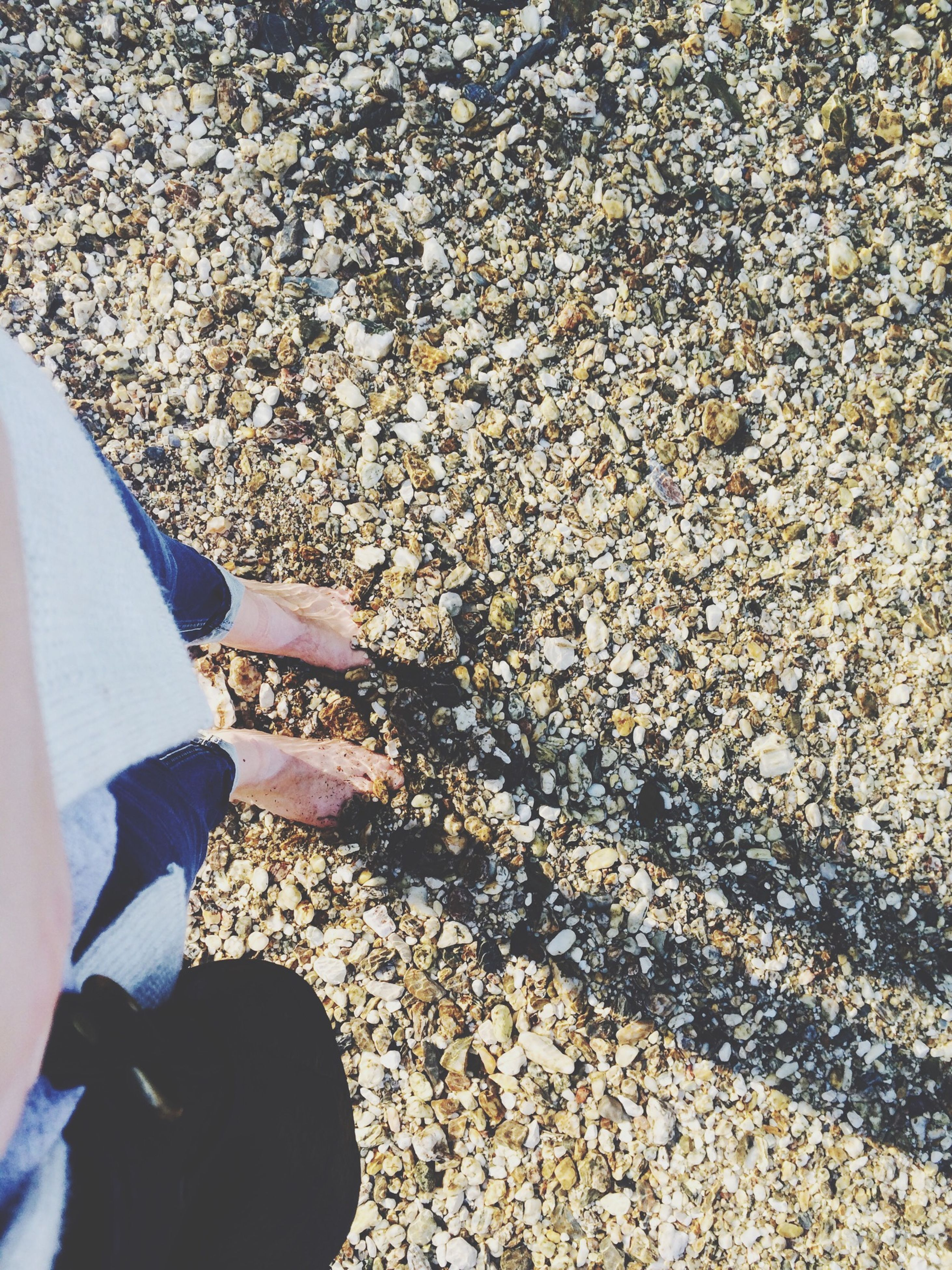 low section, person, high angle view, lifestyles, personal perspective, standing, leisure activity, shoe, part of, men, human foot, unrecognizable person, stone - object, day, sunlight, outdoors