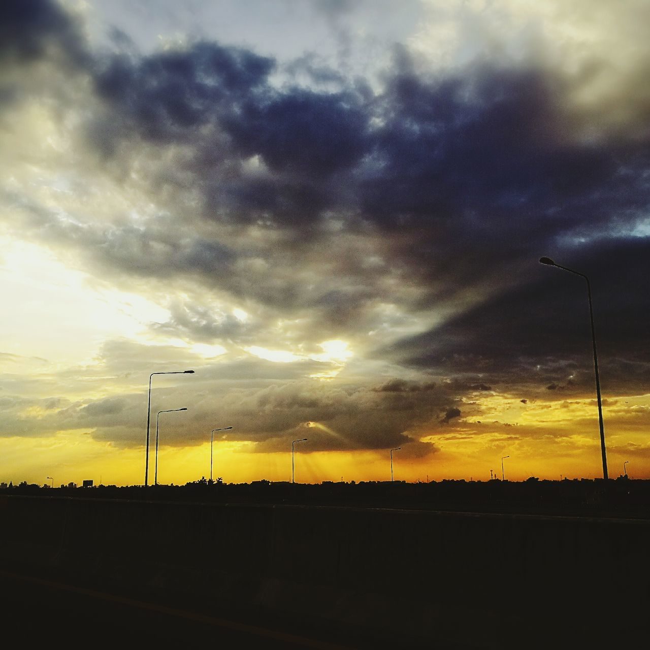 sunset, cloud - sky, sky, silhouette, no people, nature, tranquil scene, outdoors, street light, scenics, transportation, tranquility, cable, beauty in nature, landscape, road, tree, electricity pylon, telephone line, day