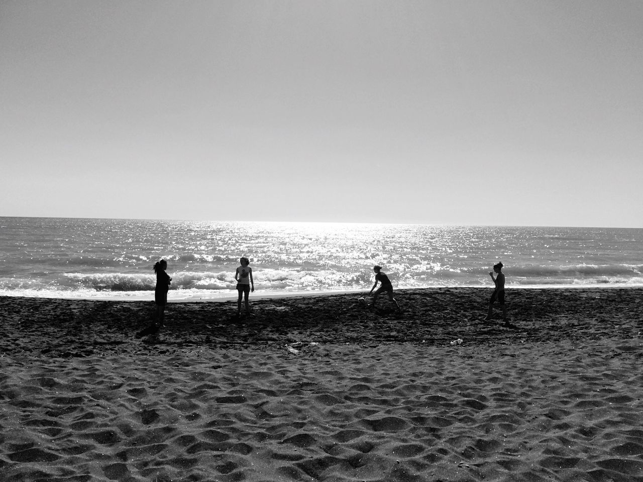 sea, beach, horizon over water, shore, sand, water, nature, wave, real people, beauty in nature, scenics, sky, vacations, standing, leisure activity, men, outdoors, clear sky, weekend activities, lifestyles, silhouette, day, people