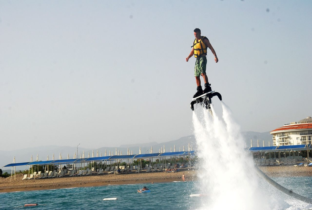 real people, adventure, leisure activity, water, full length, day, lifestyles, outdoors, risk, motion, balance, one person, vacations, splashing, speed, men, spraying, waterfront, extreme sports, mid-air, stunt, clear sky, nature, helmet, sport, mountain, sky, headwear, young adult, people