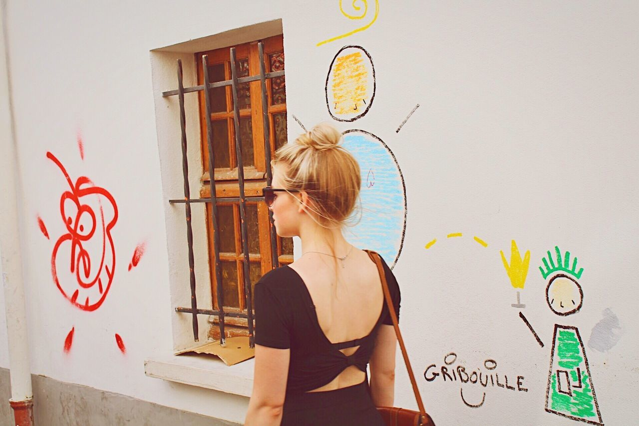 EyeEm Selects One Person Real People Hair Bun Standing Blond Hair Day Young Adult One Woman Only People Adult Streets Of Paris Wall Graffiti Female Sunny Day