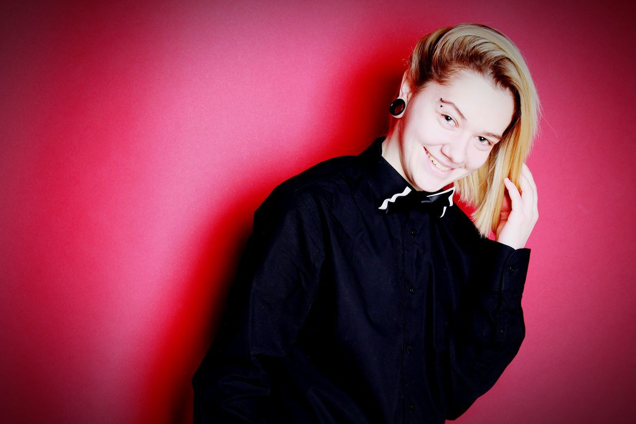 Waist Up Red Background Portrait Red Colored Background Smiling Studio Shot One Person People Pink Background Young Adult Black Color Front View Indoors  Adults Only Adult Young Women One Woman Only Long Sleeved Only Women