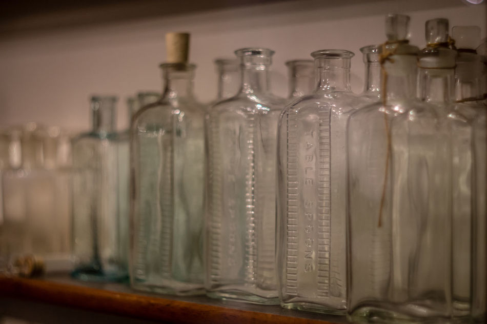 Abundance Arrangement Bottle Bottles Bottles Collection Close-up Focus On Foreground Glass - Material Group Of Objects Hanging In A Row Indoors  Large Group Of Objects Metal No People Old Old Bottle Old Bottles Order Selective Focus Shelf Side By Side Still Life Table Variation