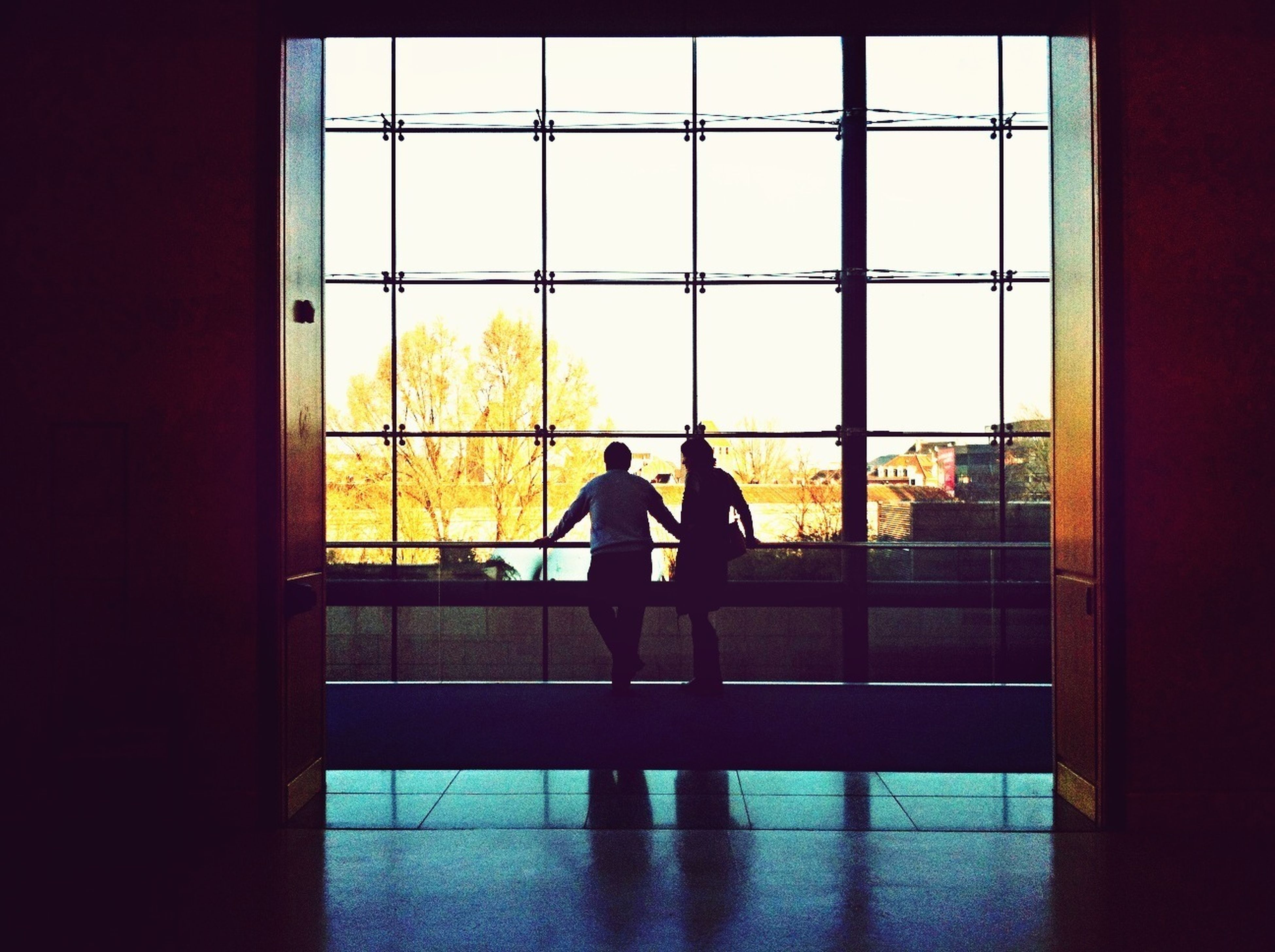 silhouette, indoors, window, men, architecture, built structure, glass - material, standing, lifestyles, sunset, rear view, looking through window, transparent, person, full length, railing, building exterior, leisure activity