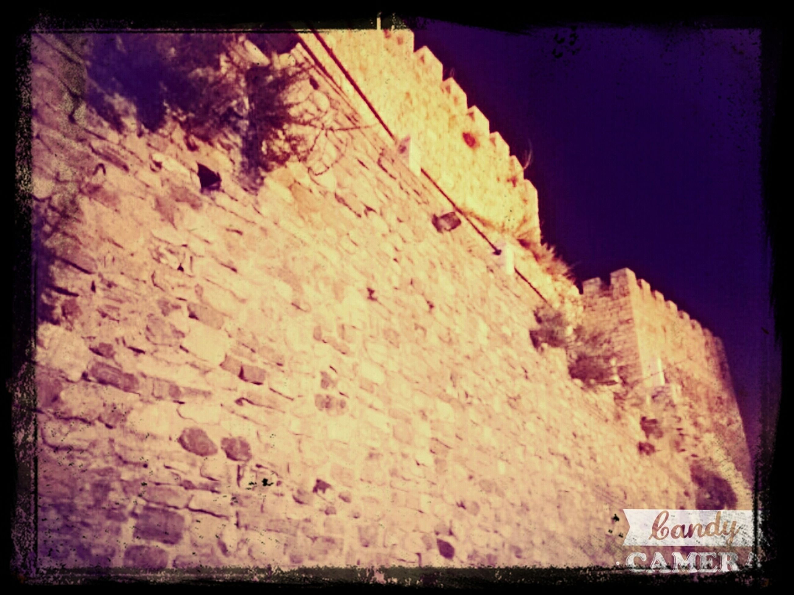 transfer print, auto post production filter, text, western script, rock formation, rock - object, low angle view, communication, wall - building feature, textured, outdoors, rough, rock, day, built structure, no people, architecture, clear sky, wall, nature