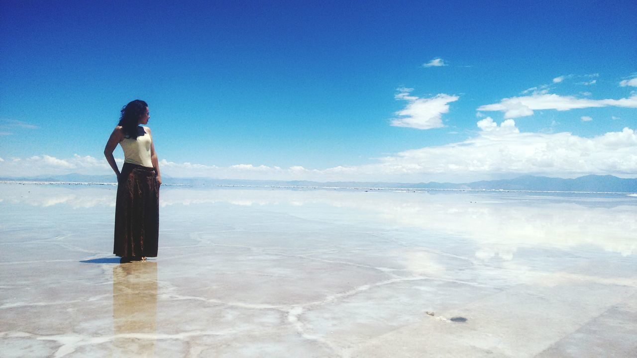 sky, salt flat, beauty in nature, scenics, day, outdoors, standing, water, sea, one person, nature, cloud - sky, reflection, tranquil scene, tranquility, blue, real people, salt basin, women, salt - mineral, full length, horizon over water, young adult, people