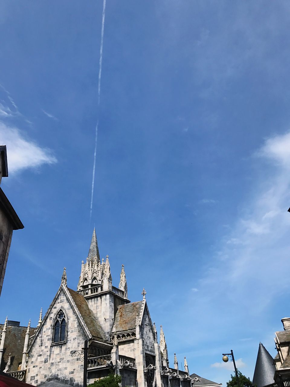 religion, architecture, place of worship, spirituality, built structure, building exterior, low angle view, day, no people, sky, outdoors, blue, vapor trail