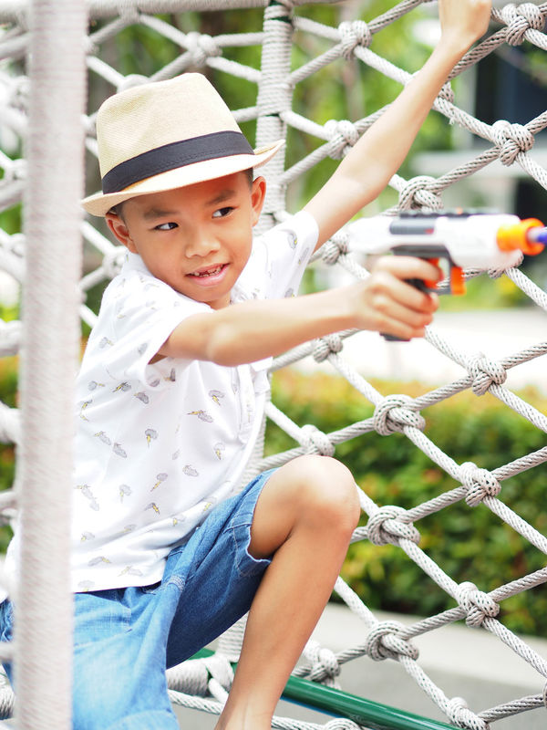 Asian boy shooting toy gun in a park. Boys Casual Clothing Childhood Cute Day Elementary Age Full Length Fun Happiness Leisure Activity Lifestyles Looking At Camera One Person Outdoors Playing Portrait Real People Sitting Smiling Asian Boy Toy Guns One Boy Only