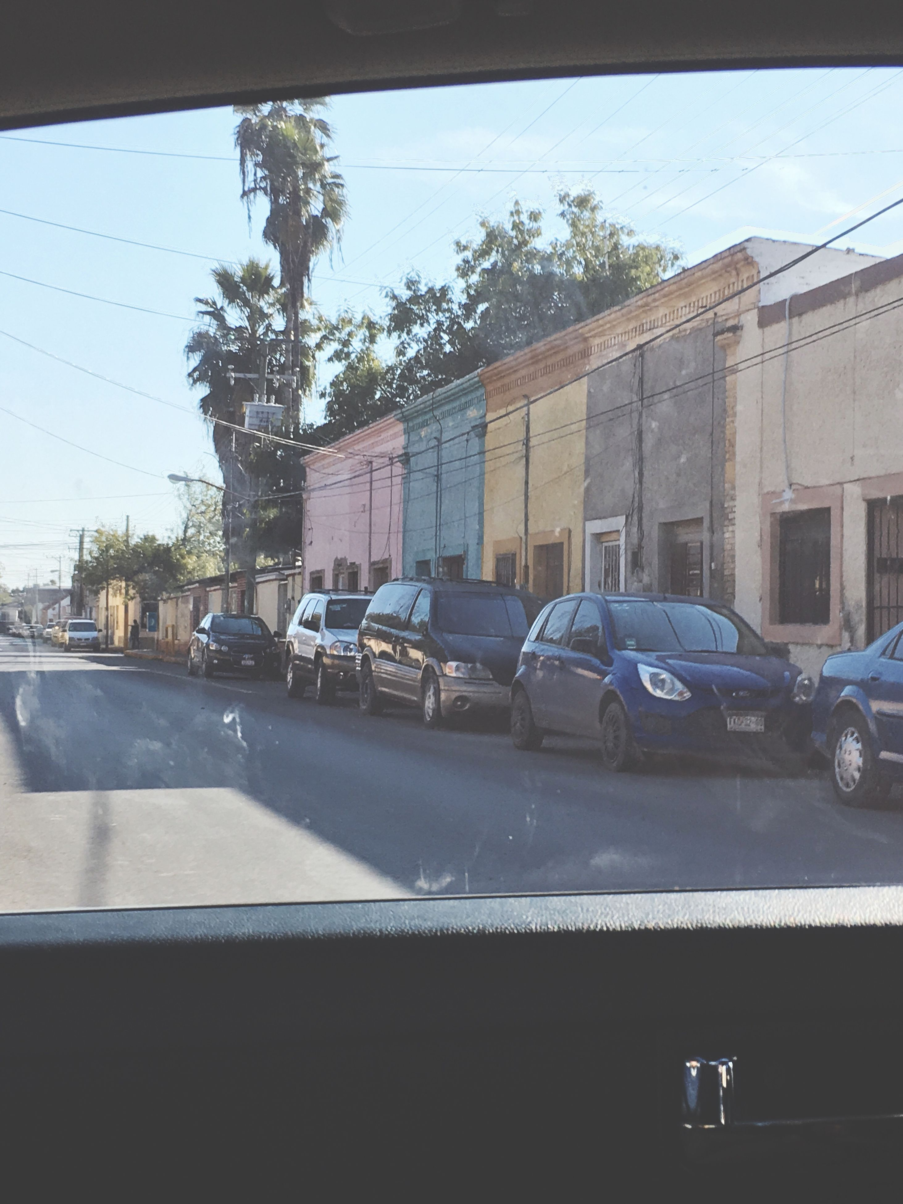 car, transportation, mode of transport, land vehicle, tree, building exterior, street, sunlight, city, built structure, architecture, parking, day, outdoors, road, no people, stationary, vehicle mirror, police car