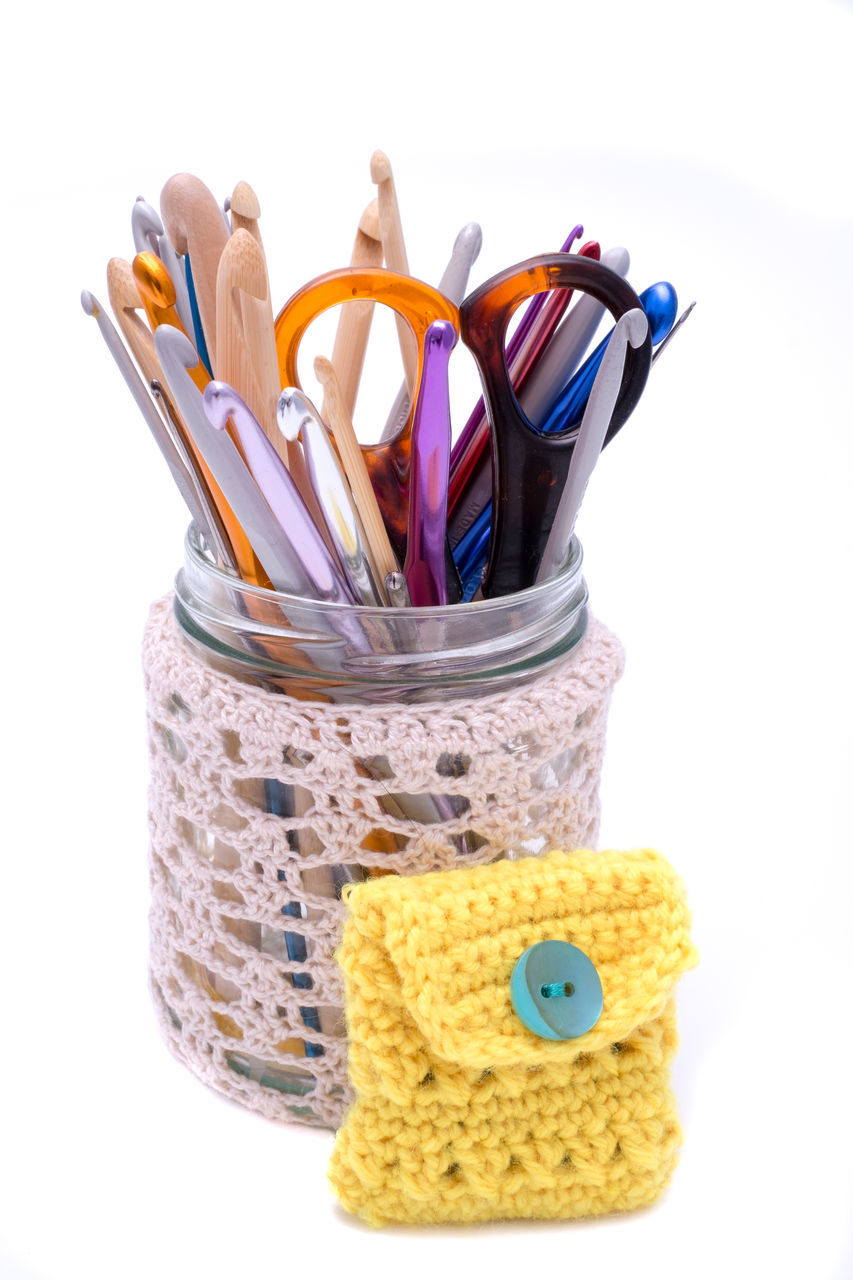 Scissor With Needlecraft Products In Container On White Background