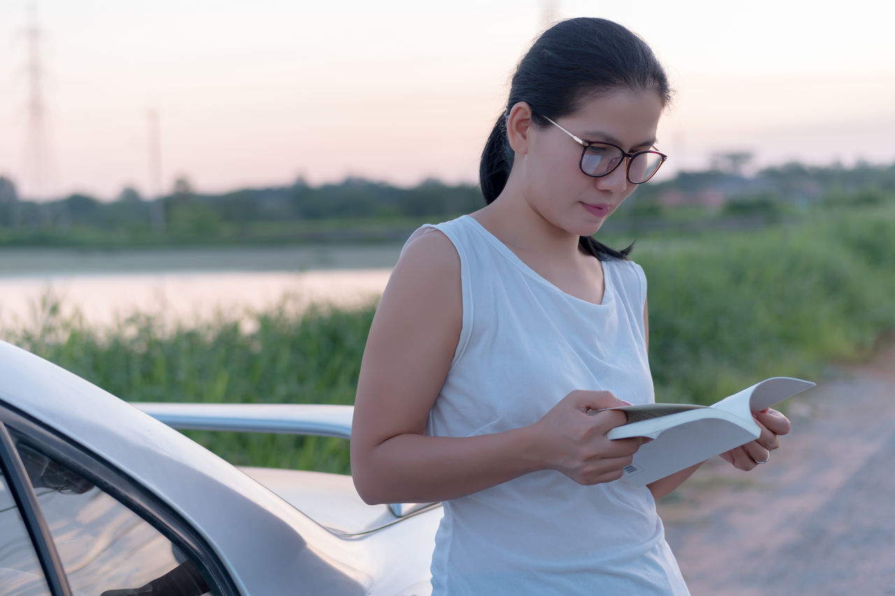 Beautiful Woman Car Casual Clothing Day Eyeglasses  Focus On Foreground Grass Holding Land Vehicle Leisure Activity Lifestyles Nature One Person Outdoors People Reading Reading A Book Real People Young Adult Young Women