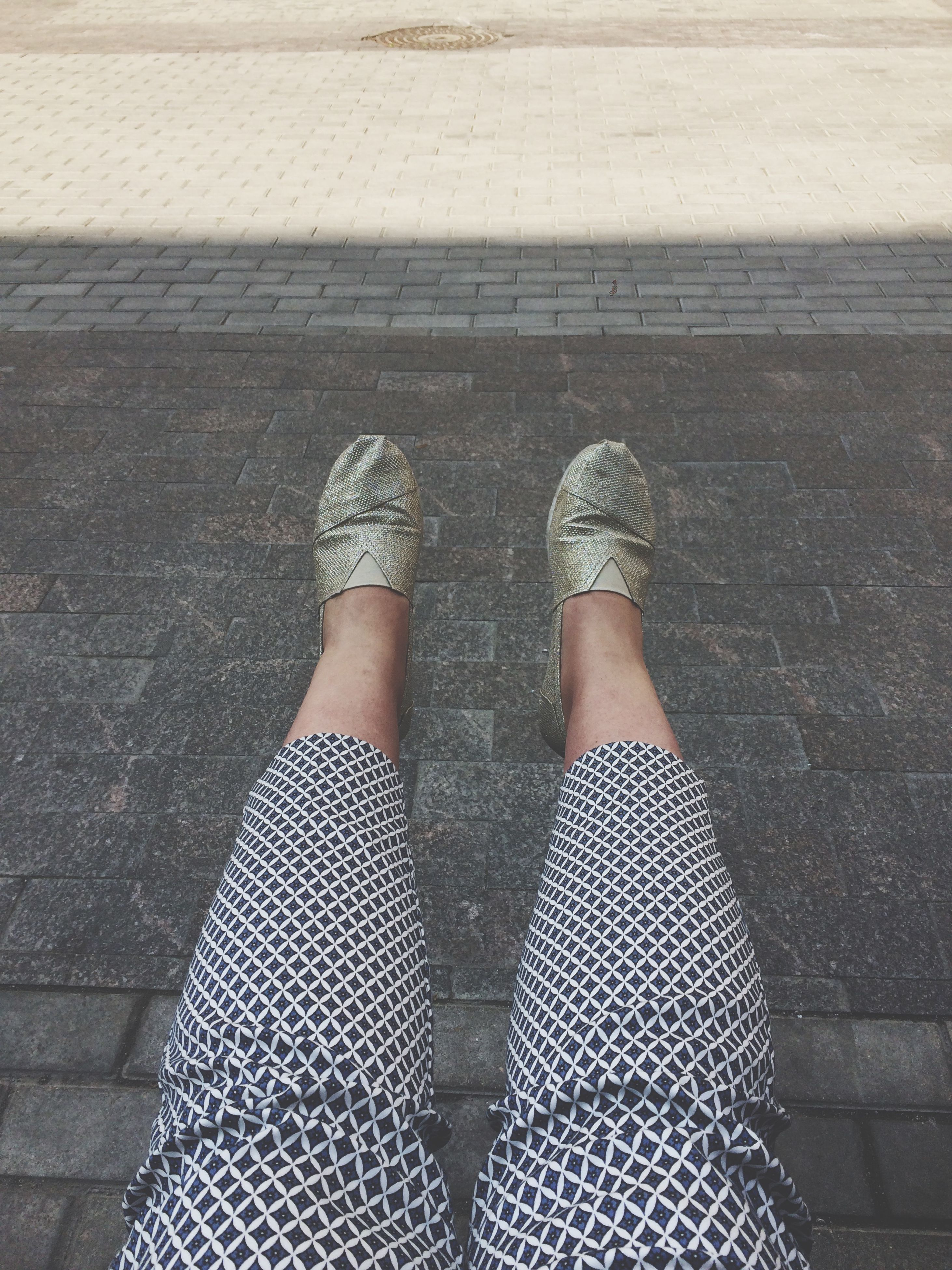 low section, person, shoe, standing, lifestyles, cobblestone, high angle view, shadow, street, sidewalk, personal perspective, sunlight, paving stone, footpath, pattern, day