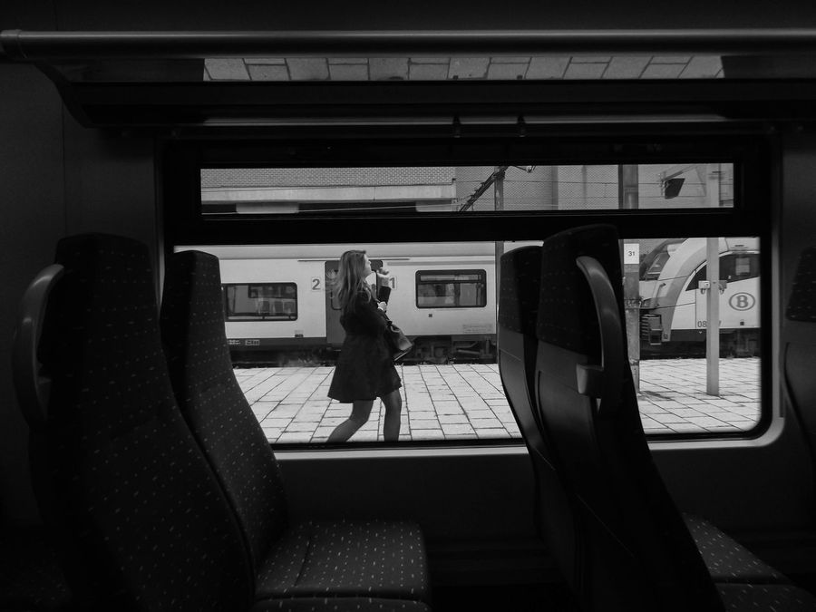 Walking By. Railway Casual Clothing Day Full Length Journey Daily Commute Land Vehicle Leisure Activity Lifestyles Candid Daily Life Mode Of Transport Passenger Public Transportation Mode Of Transportation Woman Conceptual Conceptual Photography  Bnwphotography Black And White Seat Window Reflection