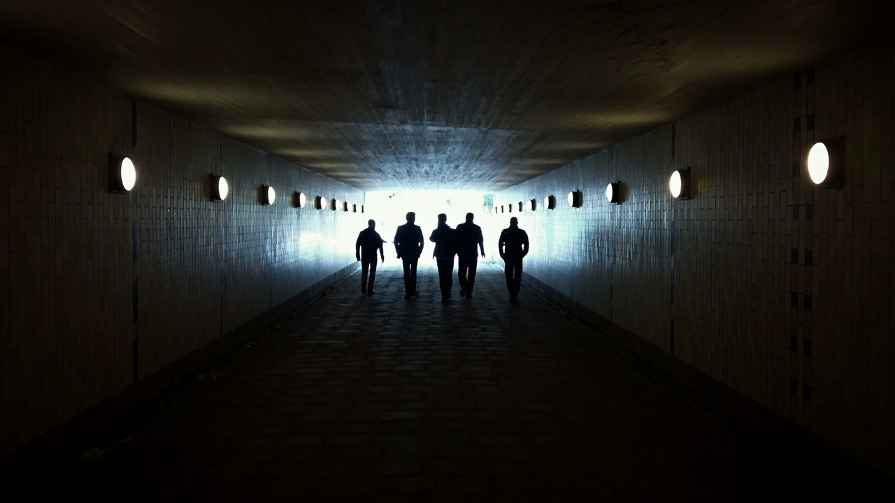 illuminated, indoors, real people, tunnel, ceiling, silhouette, architecture, underground, lighting equipment, men, light at the end of the tunnel, built structure, walking, the way forward, leisure activity, medium group of people, lifestyles, women, togetherness, standing, day, adult, people