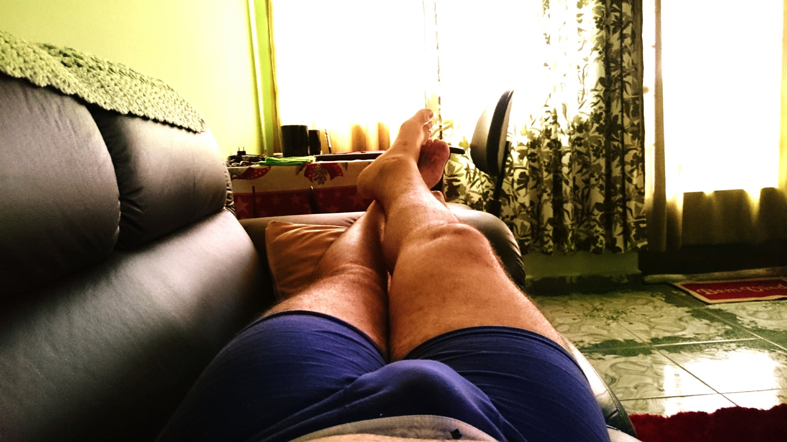 low section, person, personal perspective, lifestyles, relaxation, legs crossed at ankle, sitting, human foot, leisure activity, barefoot, sunlight, part of, resting, indoors, shoe, relaxing