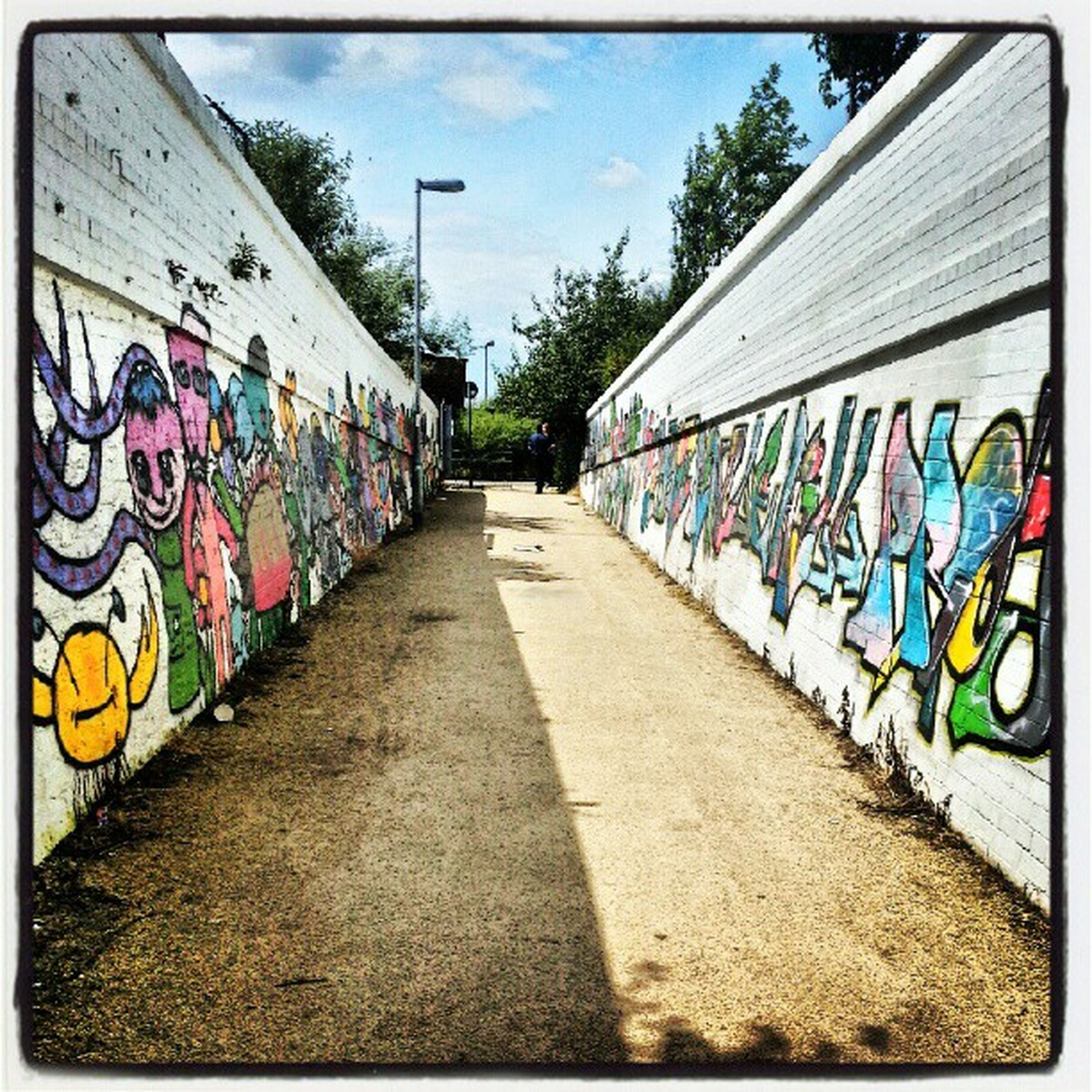 graffiti, art, art and craft, creativity, multi colored, built structure, the way forward, architecture, street art, wall - building feature, diminishing perspective, building exterior, street, sky, day, vanishing point, wall, outdoors, in a row, vandalism