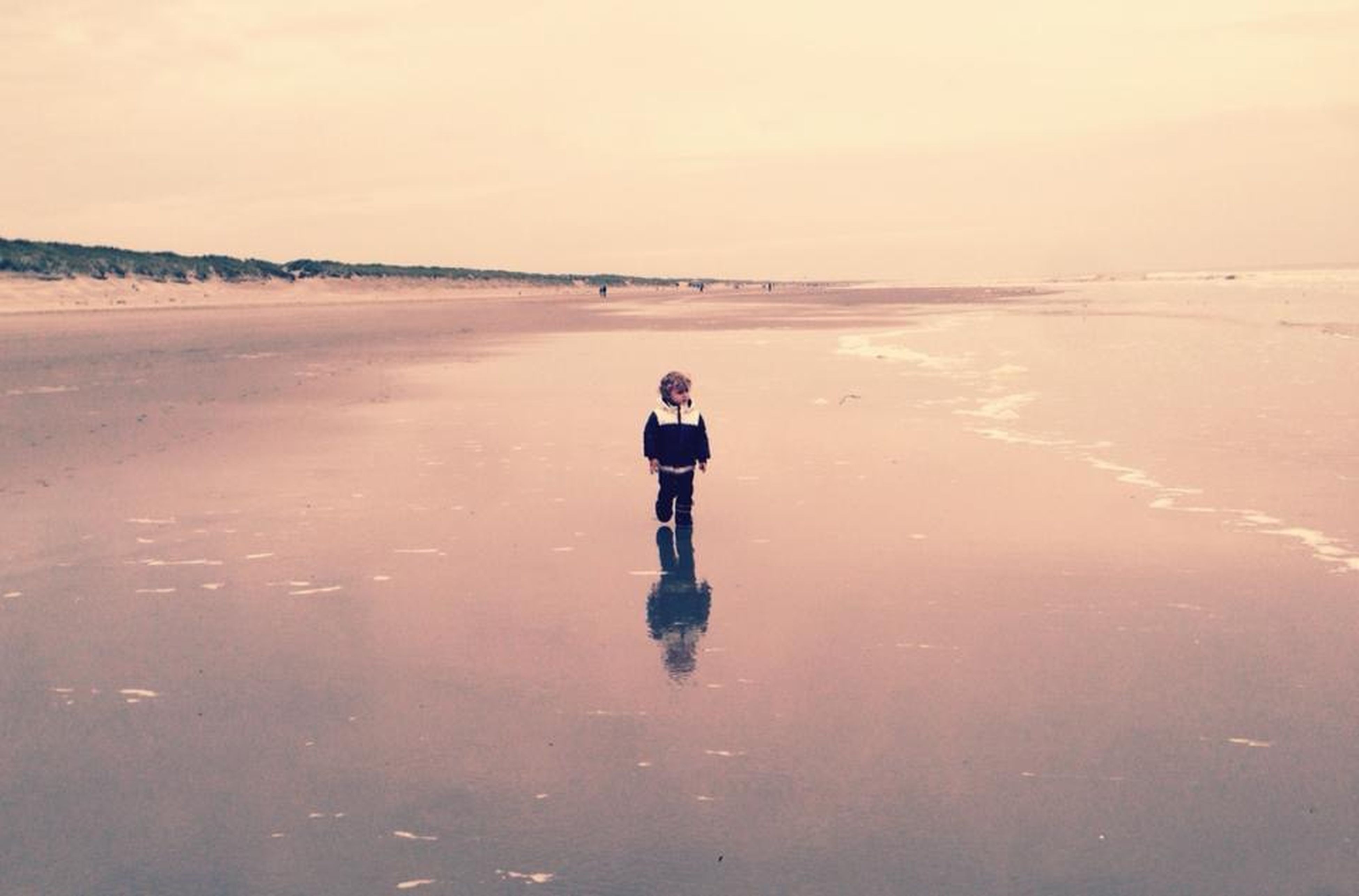 water, full length, beach, lifestyles, sea, rear view, standing, tranquility, sand, leisure activity, tranquil scene, shore, reflection, horizon over water, walking, scenics, clear sky, nature