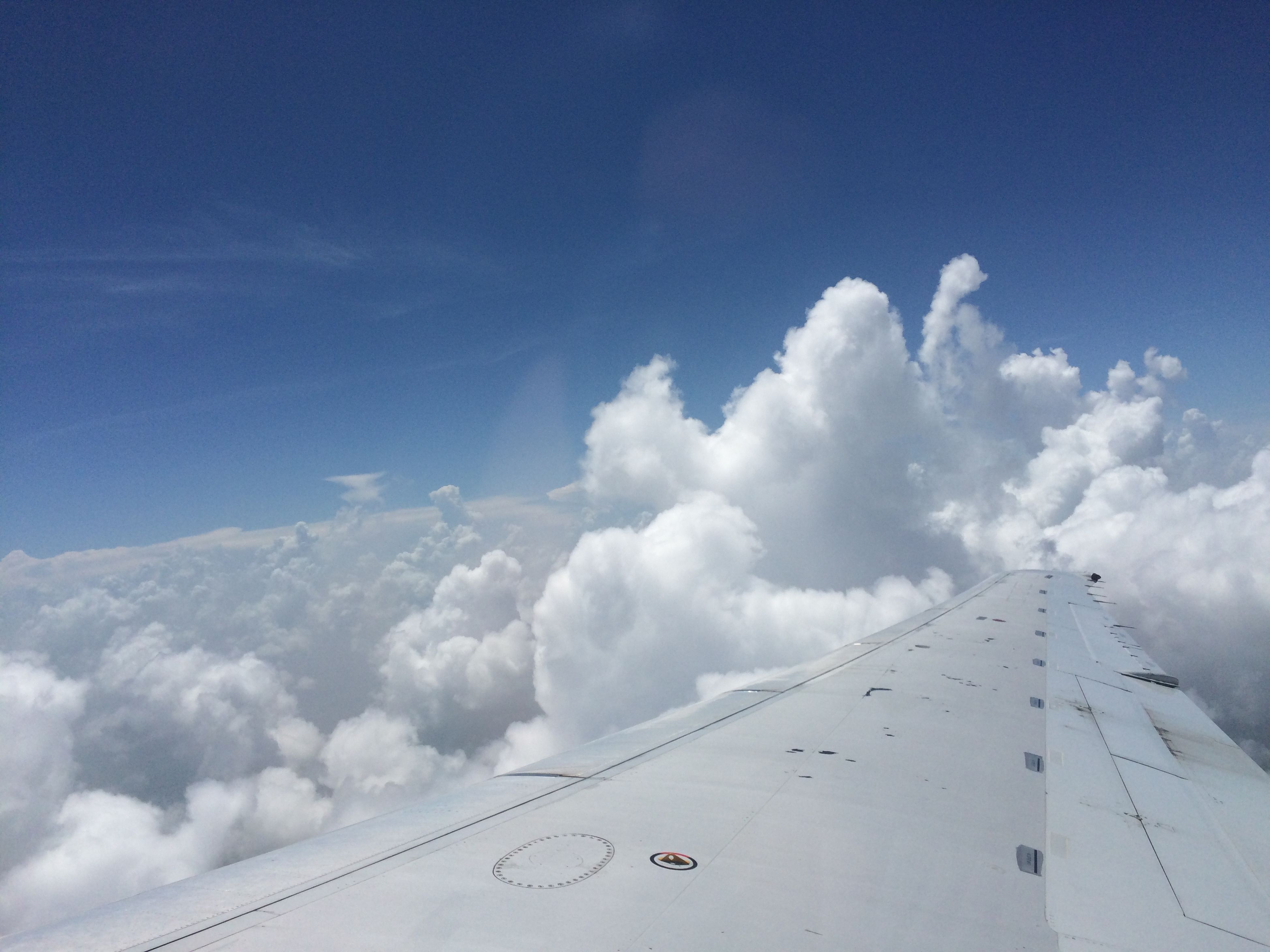 sky, low angle view, cloud - sky, blue, transportation, cloud, white color, cloudy, day, nature, outdoors, white, no people, beauty in nature, airplane, scenics, tranquility, flying, mode of transport, copy space