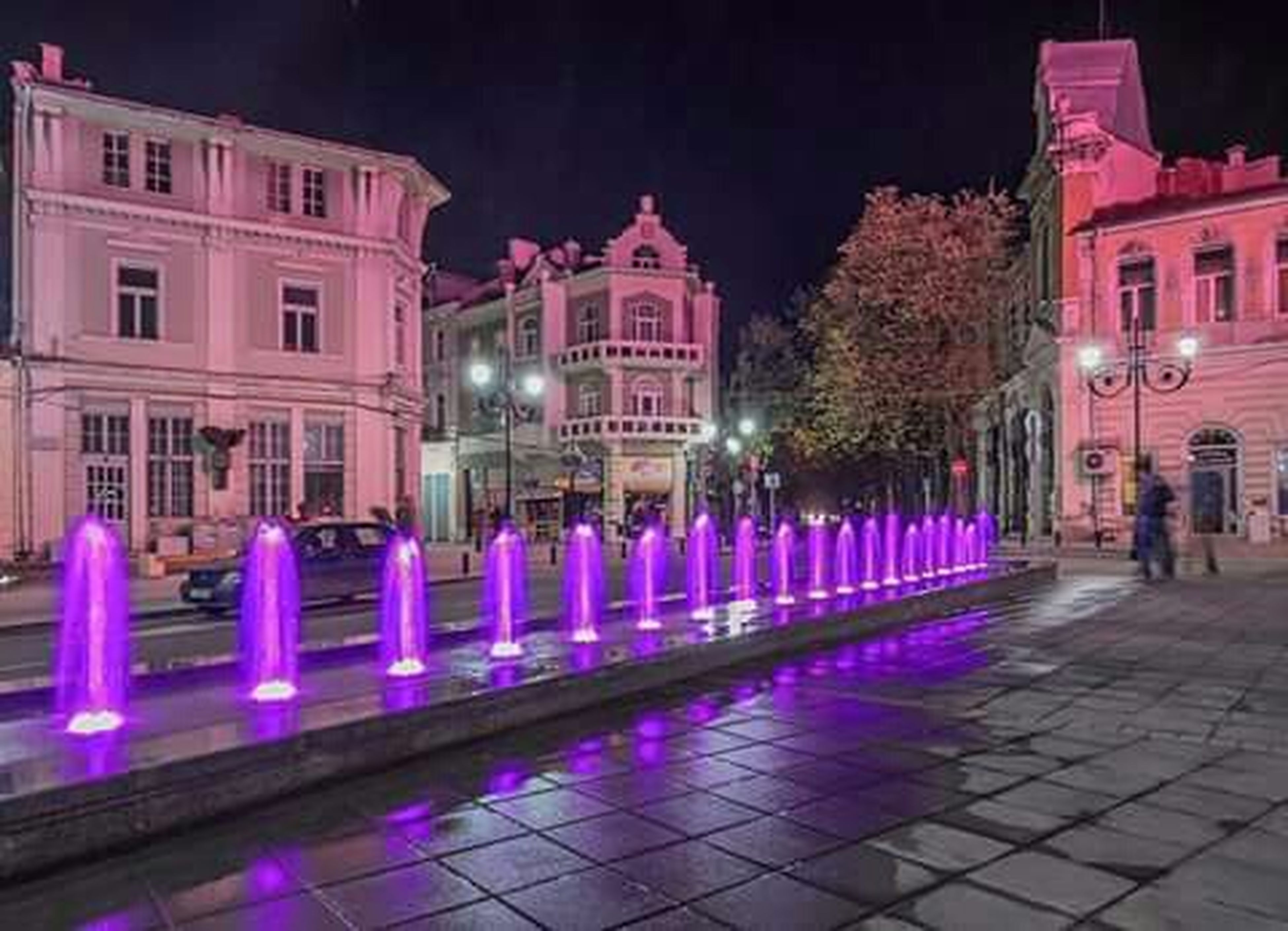 building exterior, night, illuminated, architecture, built structure, city, street, tree, street light, building, cobblestone, incidental people, outdoors, lighting equipment, facade, city life, residential building, sidewalk, residential structure, footpath