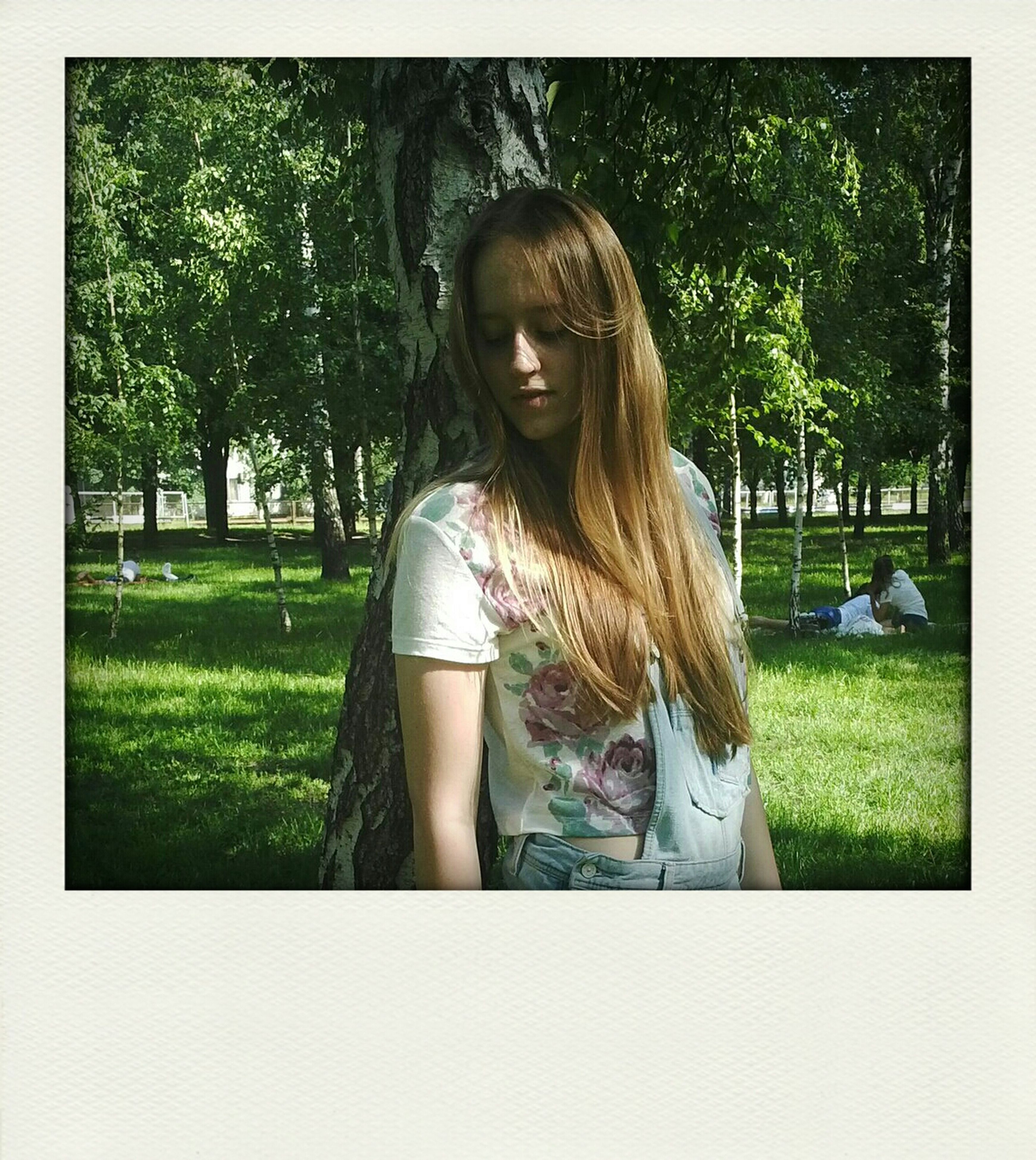 tree, young adult, grass, person, lifestyles, young women, casual clothing, leisure activity, park - man made space, long hair, portrait, standing, transfer print, looking at camera, front view, auto post production filter, park