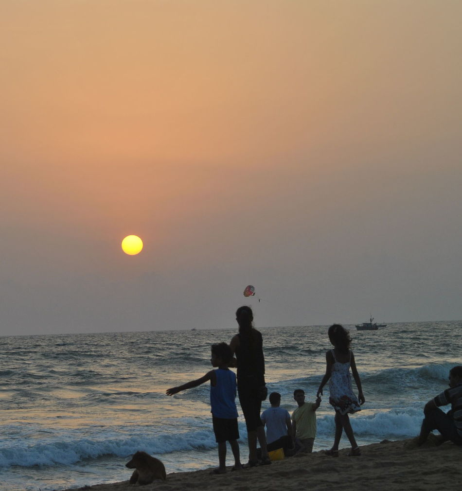 A Perfect Beach Postcard Adult Beach Beauty In Nature Boys Day Dog On Beach Dusk Falling Friendship Horizon Over Water Kids Playing On Beach Nature Outdoors Parachute People Real People Sea Sky Standing Sunset Sunset Beach Togetherness Water Goa
