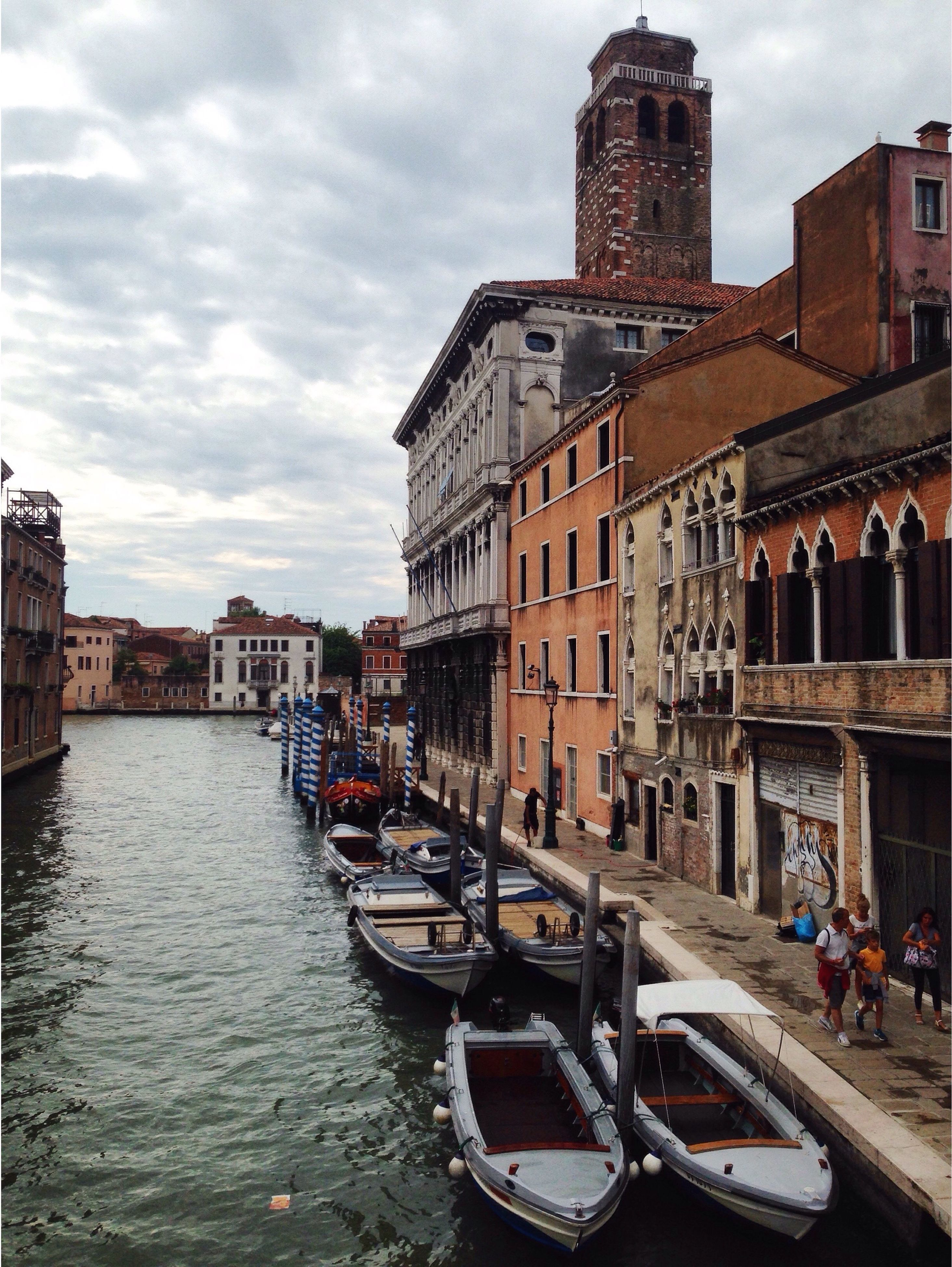 architecture, building exterior, built structure, nautical vessel, water, transportation, boat, canal, city, waterfront, sky, mode of transport, city life, travel destinations, cloud, day, culture, outdoors, gondola - traditional boat, cloud - sky, bridge, tourism, history, old town, cloudy