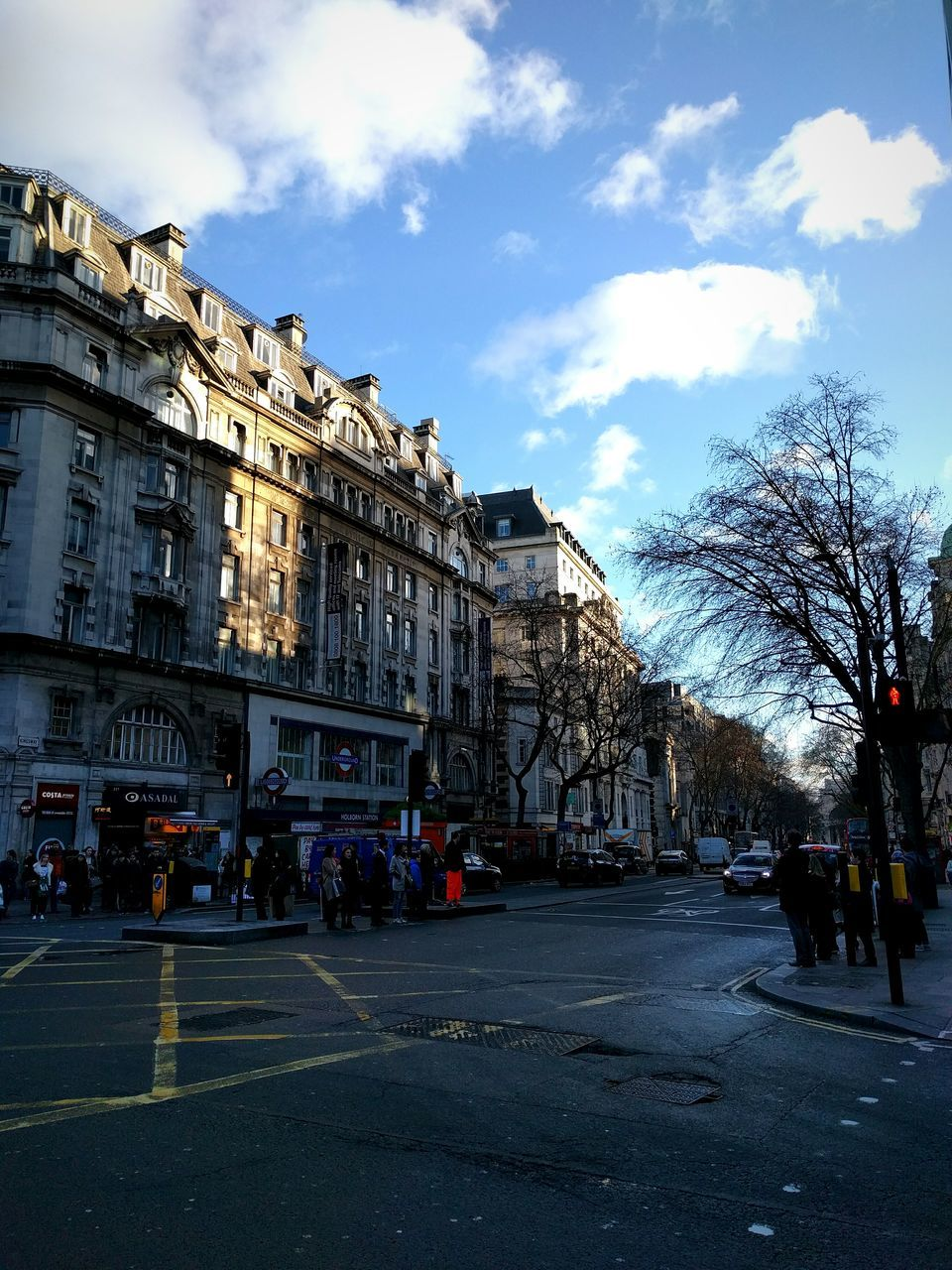 building exterior, architecture, built structure, sky, cloud - sky, street, outdoors, day, road, bare tree, travel destinations, city, large group of people, real people, tree, people
