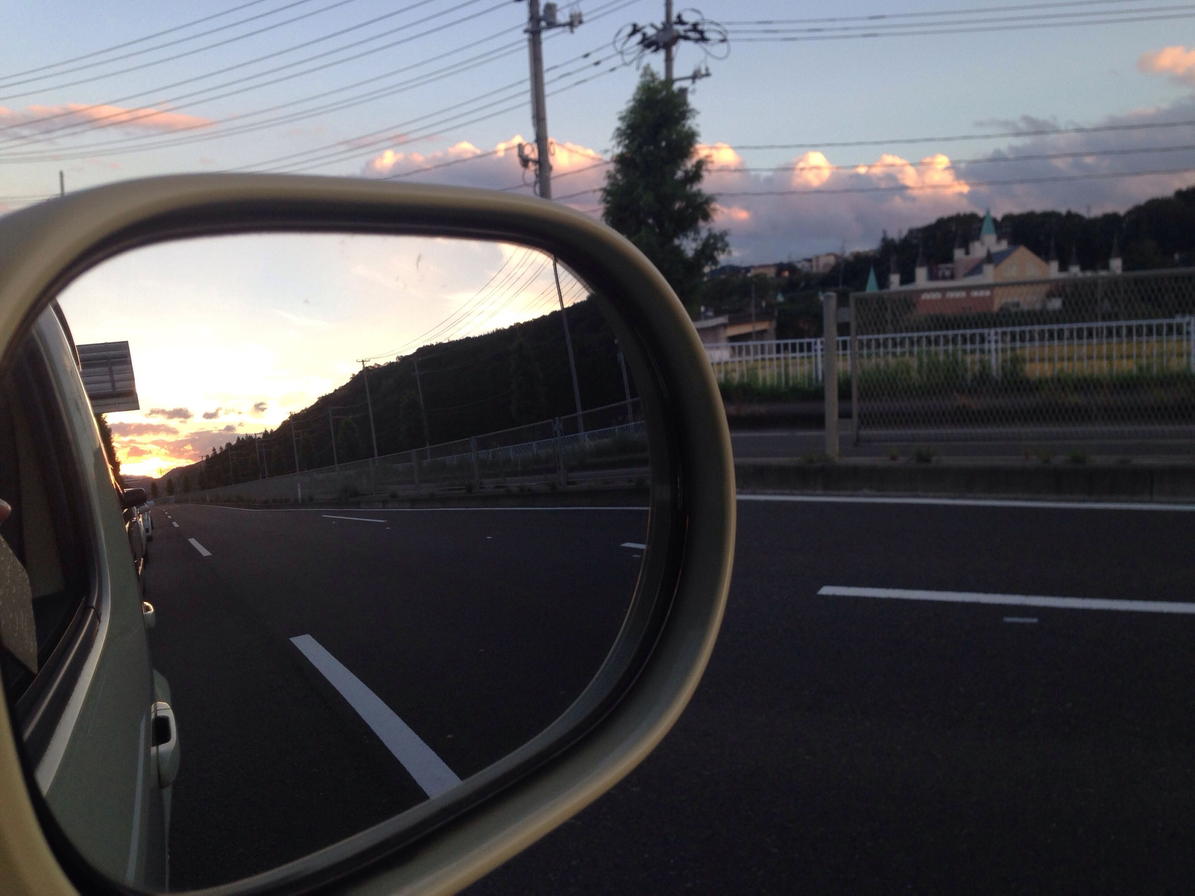transportation, sky, road, sunset, car, mode of transport, land vehicle, side-view mirror, street, cloud - sky, reflection, landscape, tree, cloud, no people, outdoors, circle, transparent, vehicle interior, travel