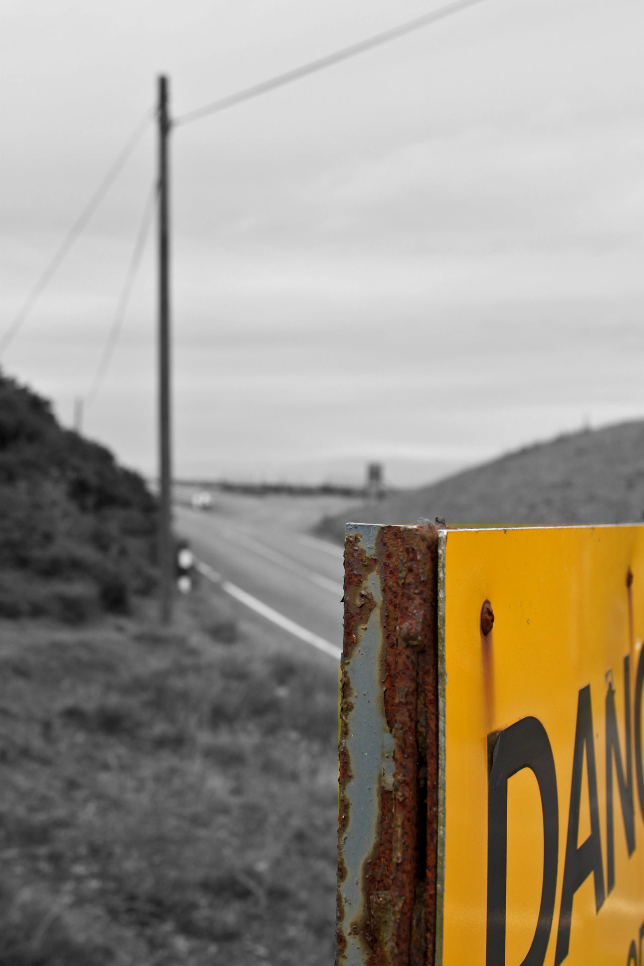 Abstract view of a danger sign near Clee Hill Quarry. Black & White Black And White Blackandwhite Britain Clee Hill Cloud Cloud - Sky Clouds Common Danger Sign Danger Signs Focus On Foreground Landscape Landscapes Road Rust Rusty Shropshire Shropshire Hills Sign Signs Sky Splash Of Color Telegraph Pole Yellow First Eyeem Photo