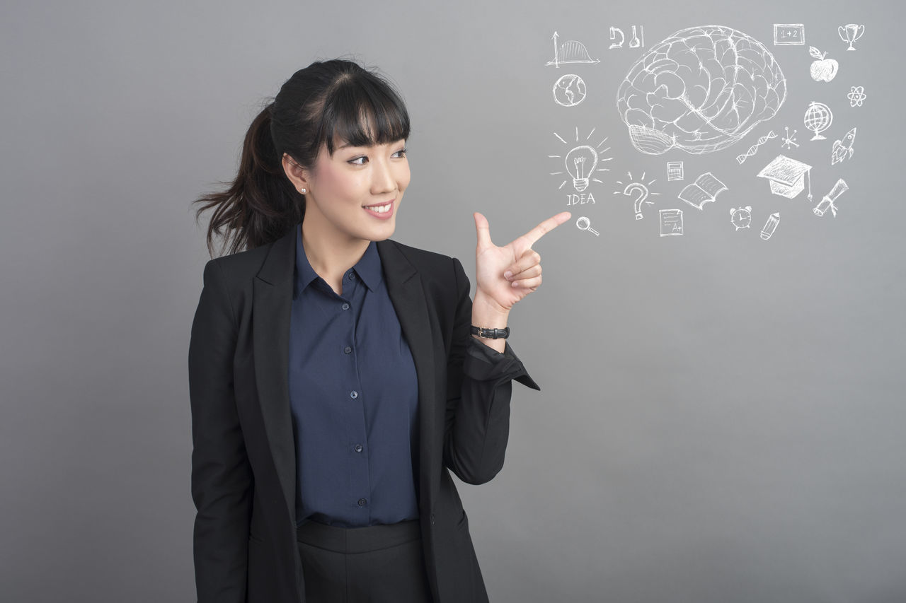 looking at camera, smiling, studio shot, suit, one person, well-dressed, portrait, indoors, young adult, business, standing, businesswoman, happiness, blackboard, corporate business, young women, day, people