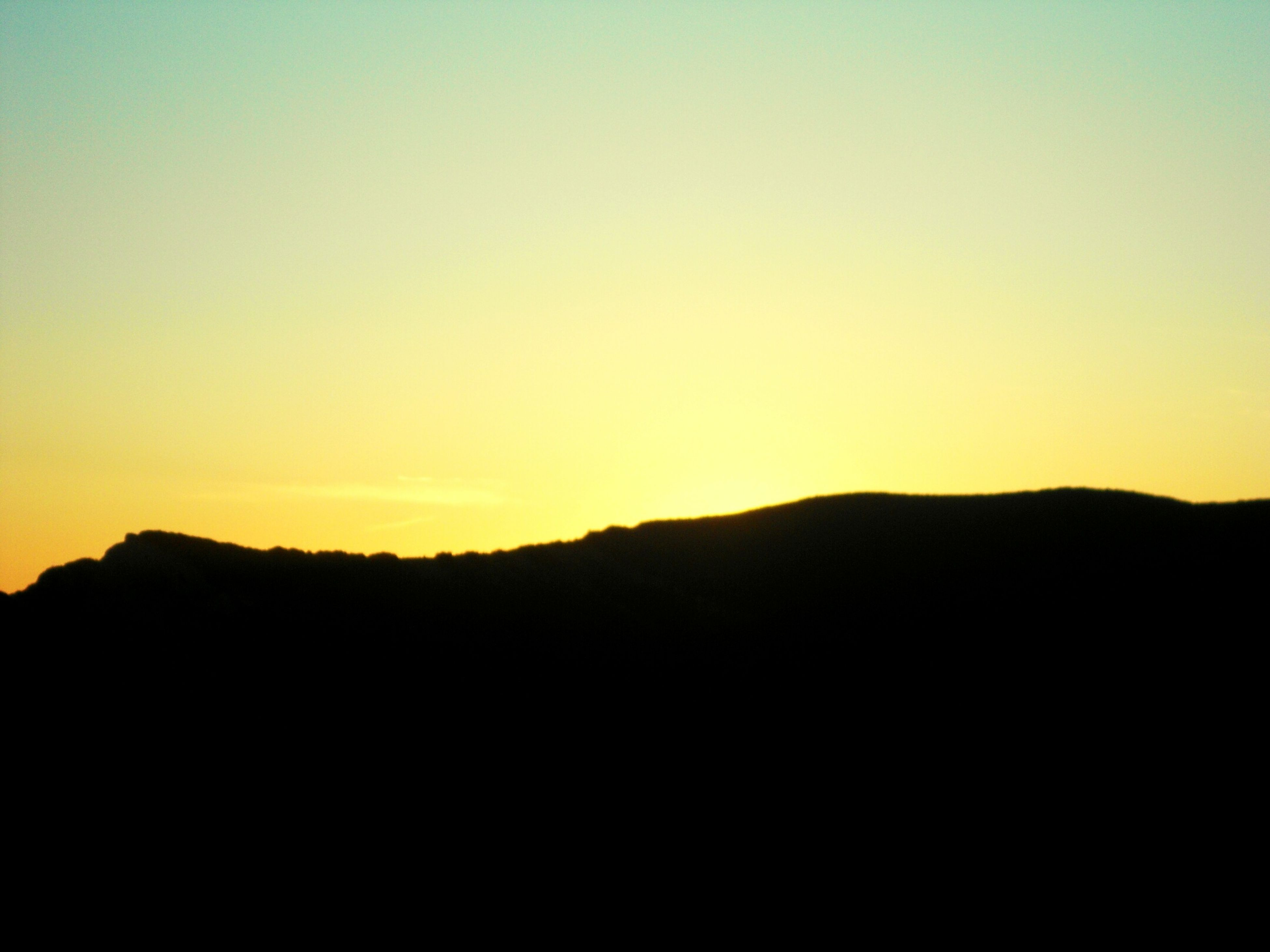 copy space, silhouette, sunset, clear sky, tranquil scene, scenics, tranquility, mountain, beauty in nature, nature, idyllic, orange color, landscape, mountain range, dark, dusk, outdoors, outline, sky, no people
