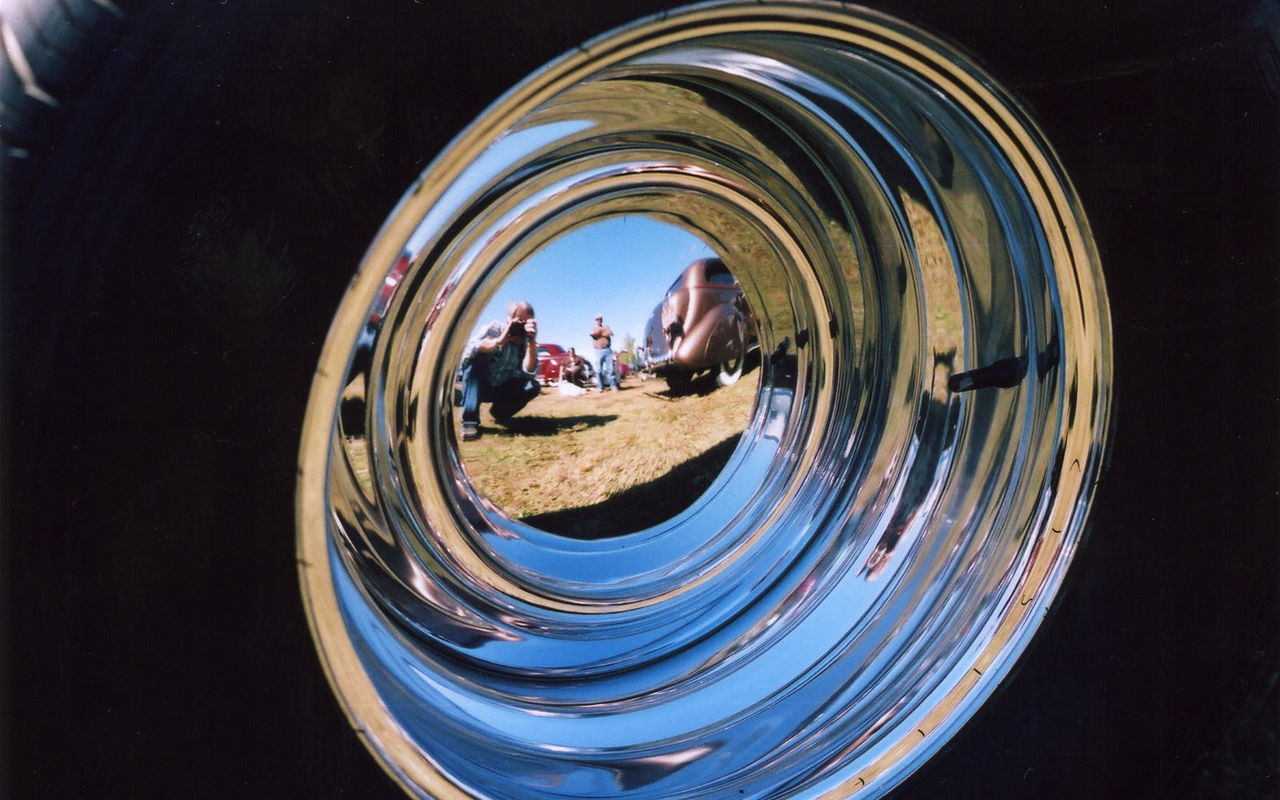 Reflection Of Man Photographing Tire