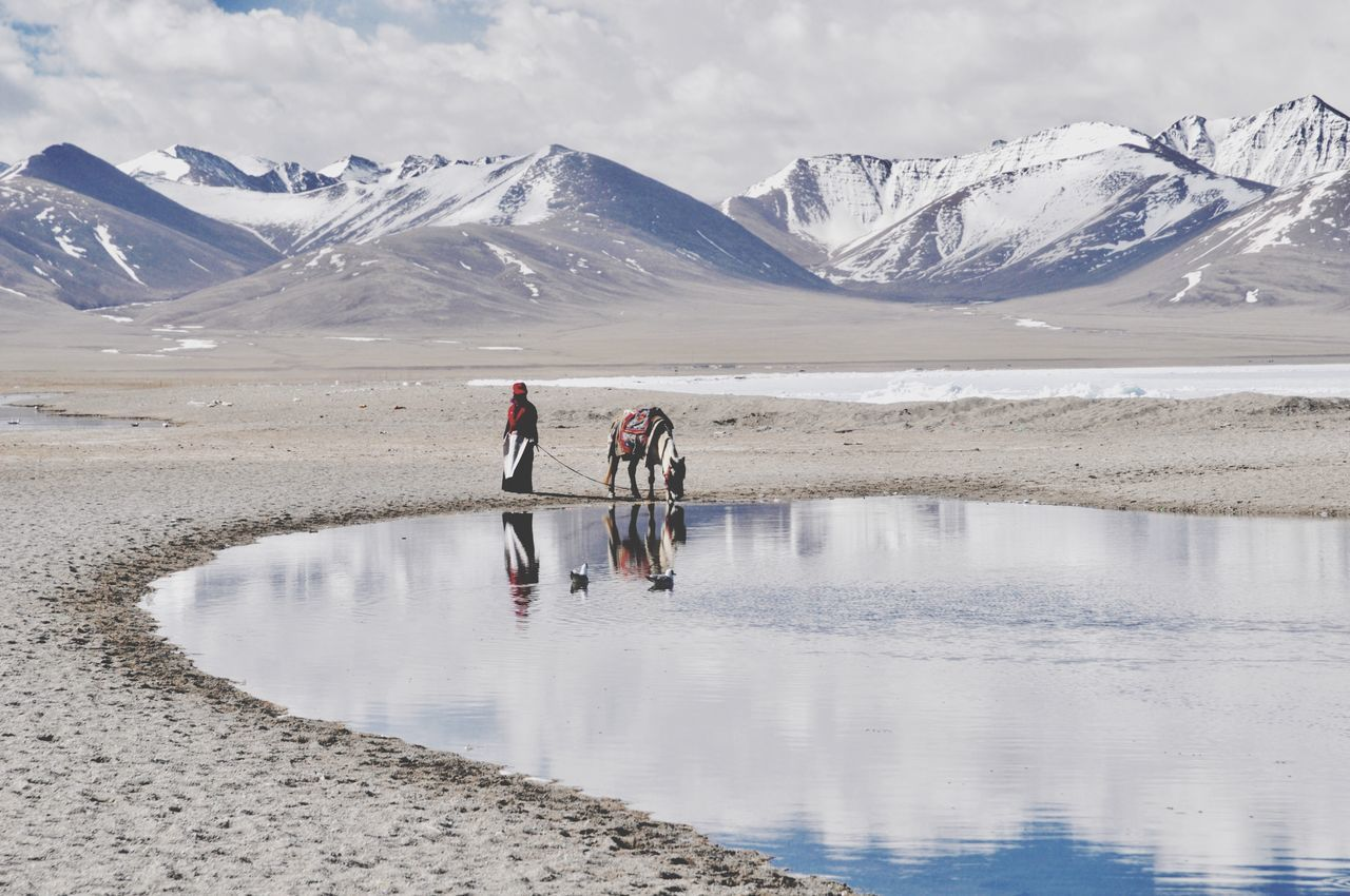 mountain, reflection, two people, lake, full length, snow, scenics, real people, togetherness, nature, day, water, beauty in nature, men, occupation, outdoors, cold temperature, snowcapped mountain, glacier, winter, sky, working, salt basin, salt - mineral, adult, people