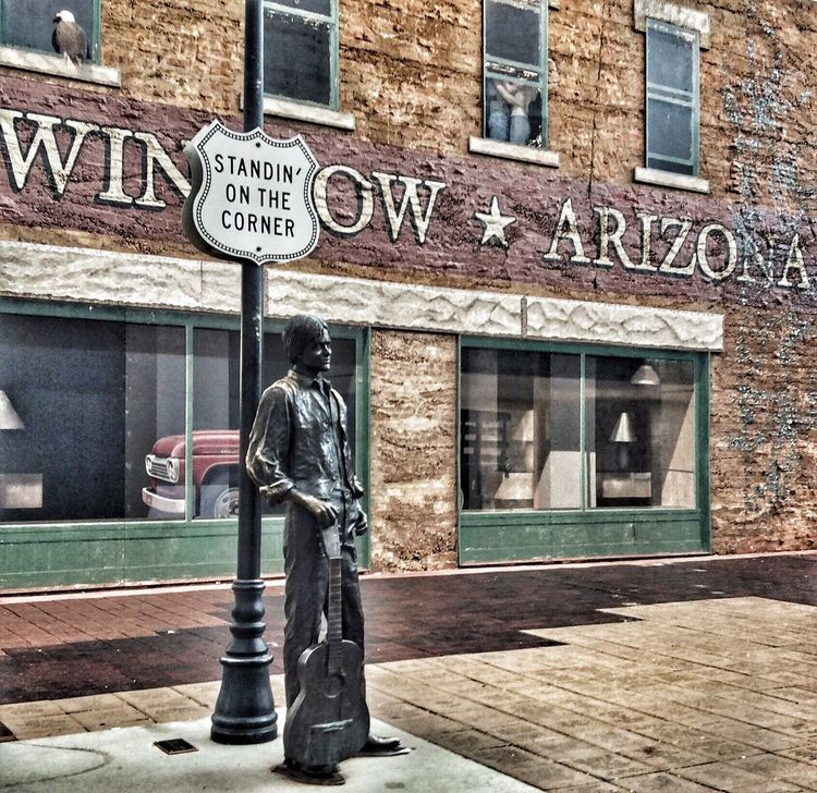 Architecture Building Exterior Built Structure Text Western Script Side View Standing Communication Information Sign Full Length City Roadside Casual Clothing Bag Outdoors Day Winslow Az Arizona The Eagles Iconic Town Tourism Atmospheric Mood Scenics In Front Of