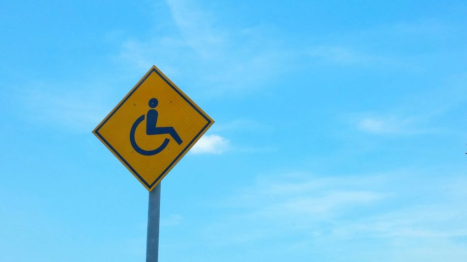 Handicapped sign on the blue sky background Sky Road Sign Handicapped Blue Yellow Clear Sky Low Angle View No People Outdoors Day Scenics Eye4photography  EyeEm Nature Lover EyeEm Best Shots EyeEm Gallery EyeEmBestPics Getty X EyeEm Copy Space Communication Business Art Background Shape People