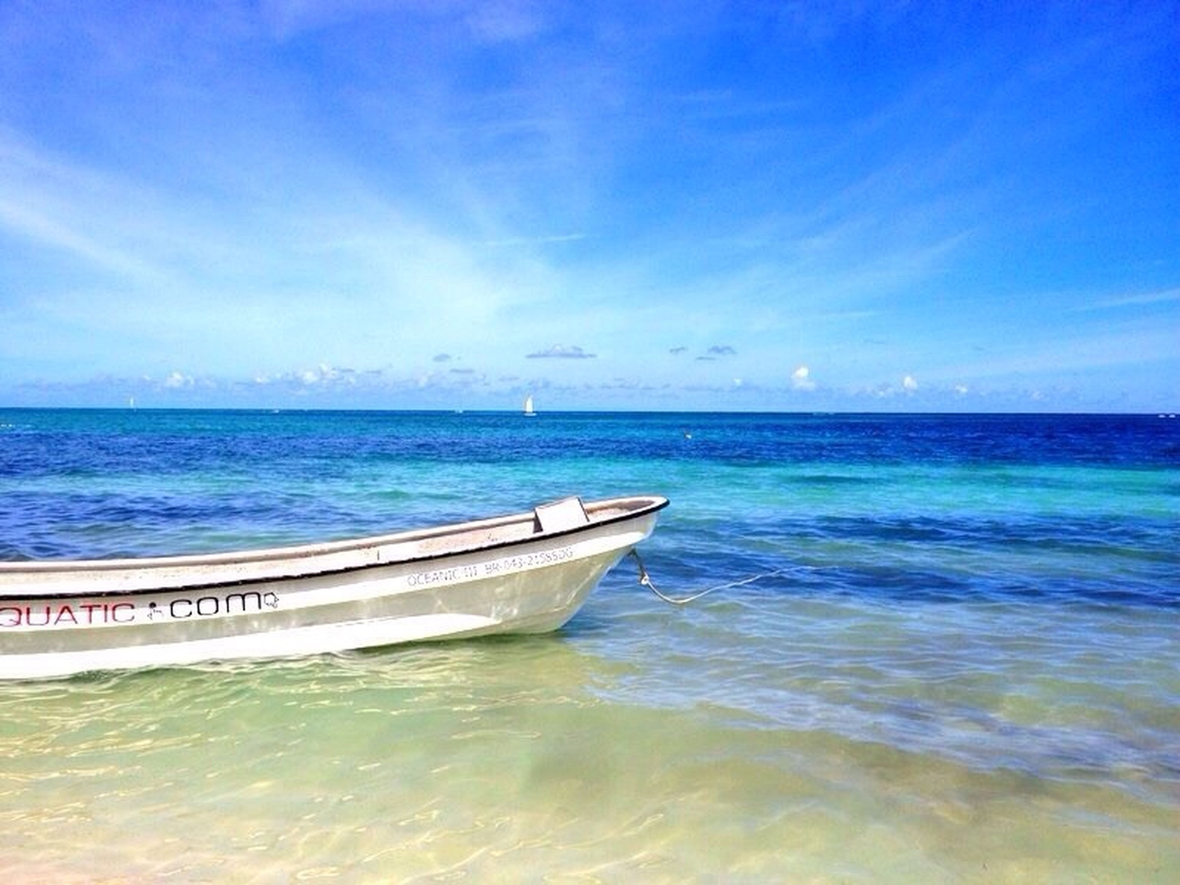 sea, water, horizon over water, nautical vessel, sky, blue, transportation, tranquil scene, tranquility, boat, beauty in nature, scenics, mode of transport, nature, waterfront, idyllic, seascape, rippled, beach, day