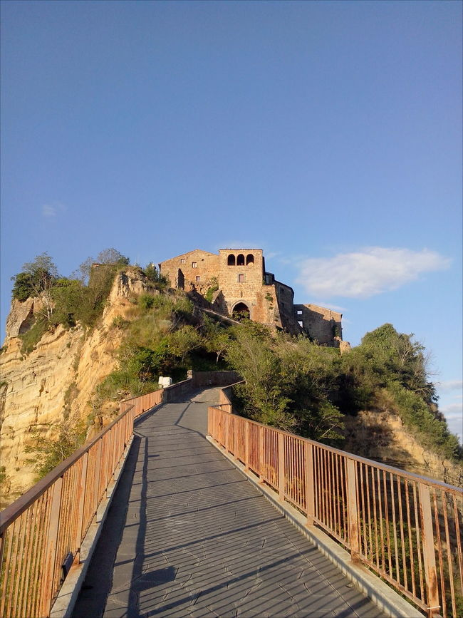 Ancient Architecture Architecture Blue Blue Sky Bridge - Man Made Structure Built Structure Civita Di Bagnoregio Cloudy Sky Day Handrails Leading Mountain No People On Top Of A Mountain Outdoors Pavement Shadows & Lights Sky The City That Is Dying The Way Forward Tuff Tufo Under The Sun Vegetation World Monuments Watch