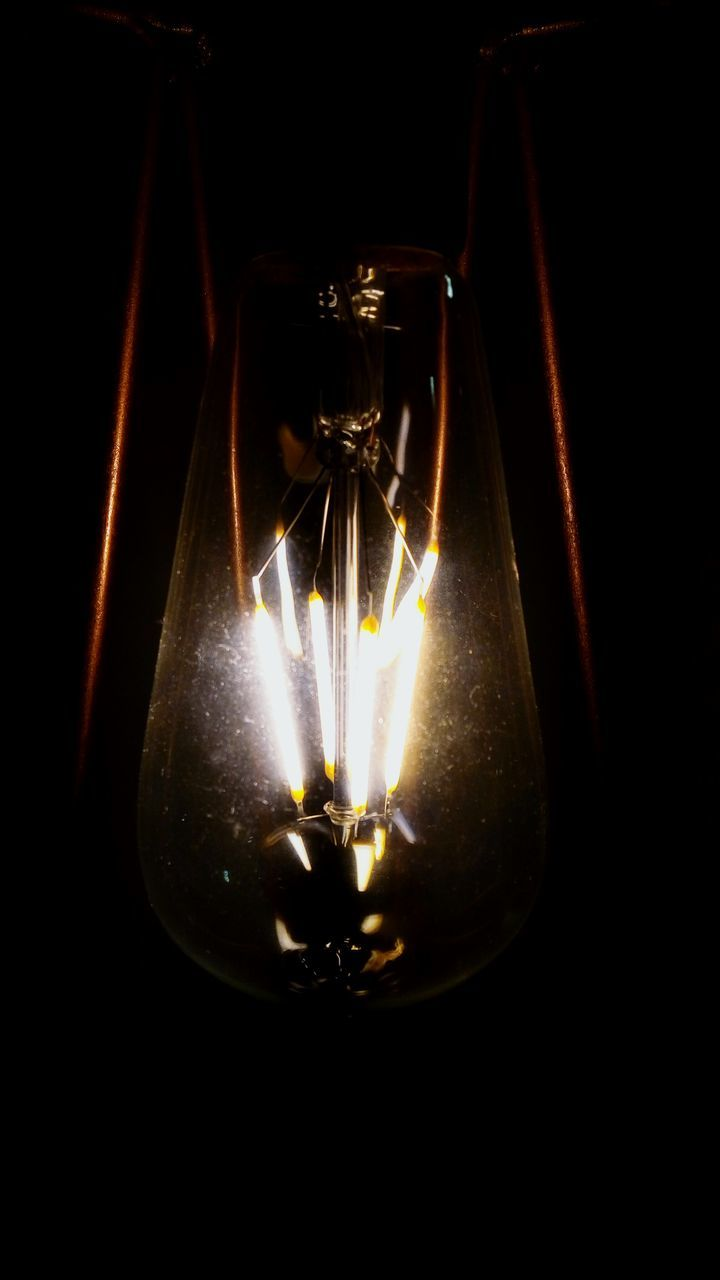 lighting equipment, glowing, illuminated, electricity, black background, light bulb, filament, no people, close-up, darkroom, studio shot, indoors, technology, flame