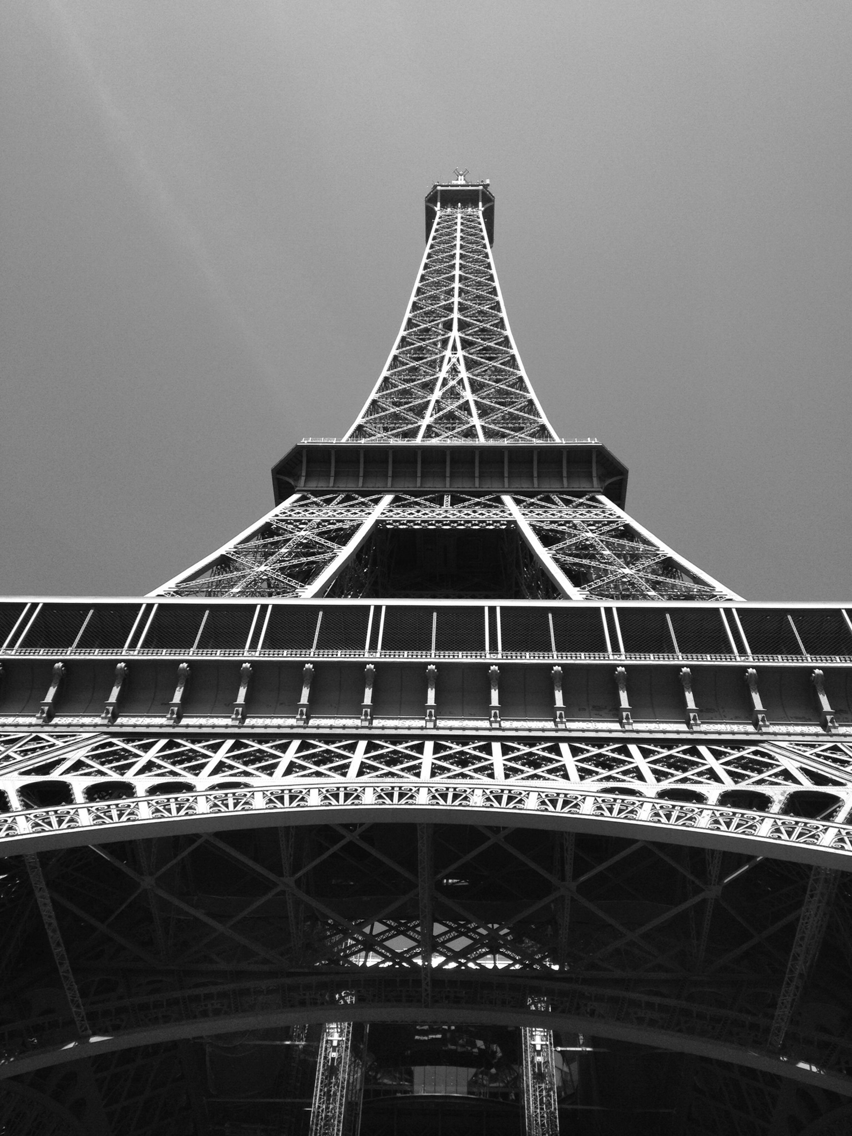 low angle view, international landmark, famous place, architecture, built structure, eiffel tower, travel destinations, tower, metal, capital cities, tall - high, tourism, travel, culture, clear sky, metallic, architectural feature, sky, communication, city