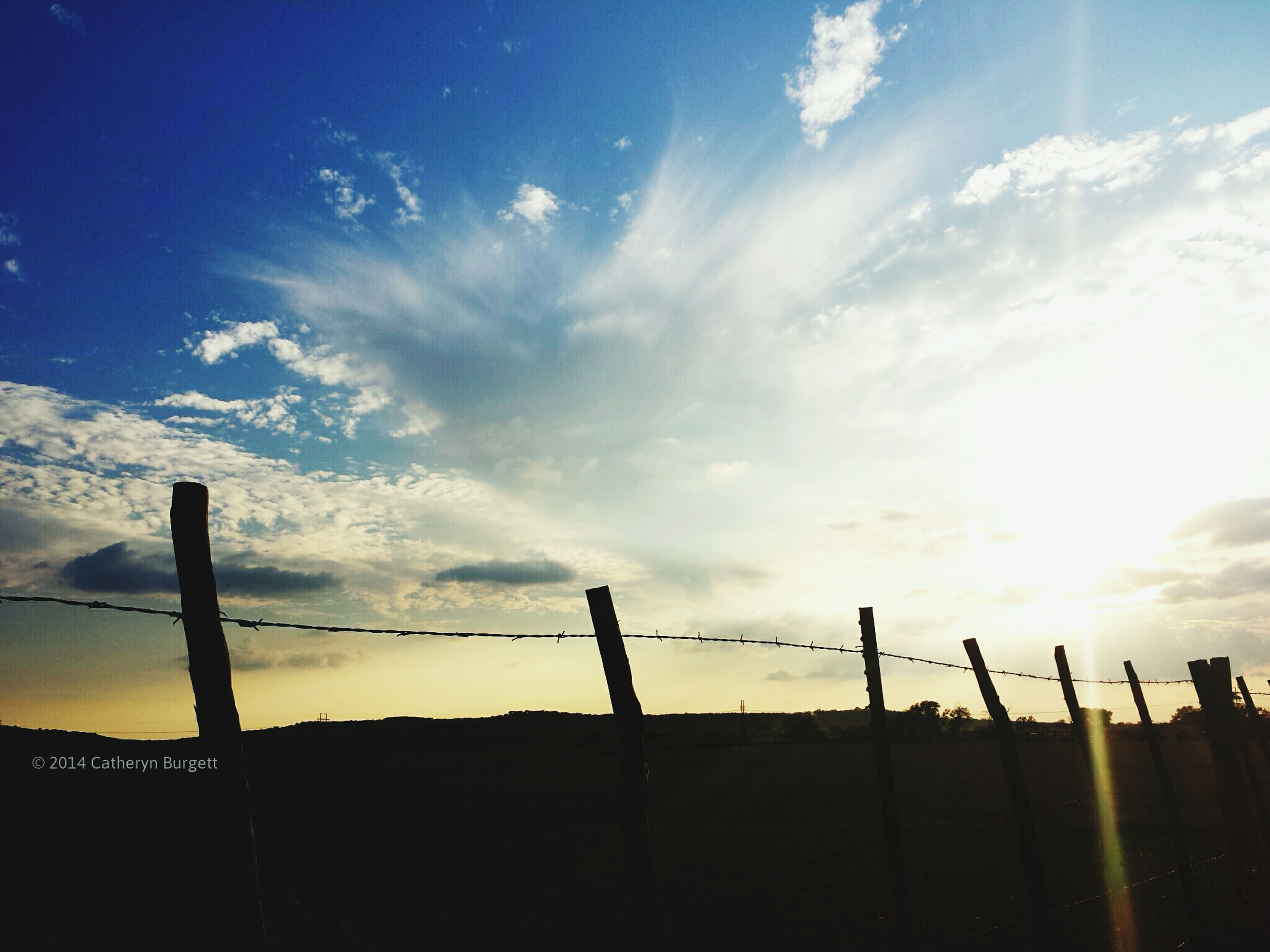 silhouette, sky, fence, cloud - sky, low angle view, sunset, protection, safety, cloud, tranquility, nature, security, beauty in nature, scenics, sunlight, tranquil scene, outdoors, cloudy, dusk, no people