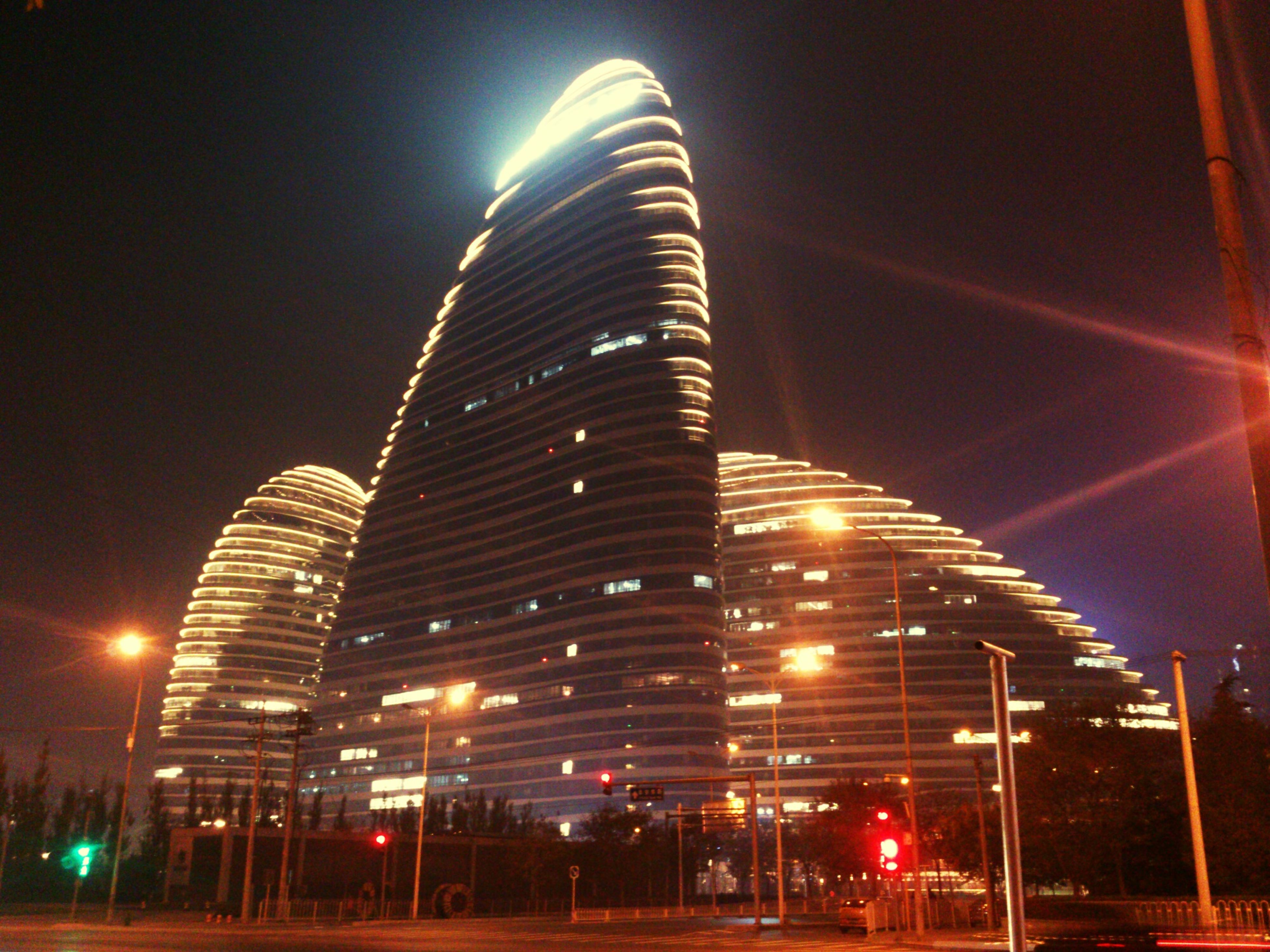 illuminated, night, architecture, built structure, building exterior, low angle view, city, modern, street light, skyscraper, lighting equipment, sky, office building, building, tall - high, street, transportation, long exposure, road, city life