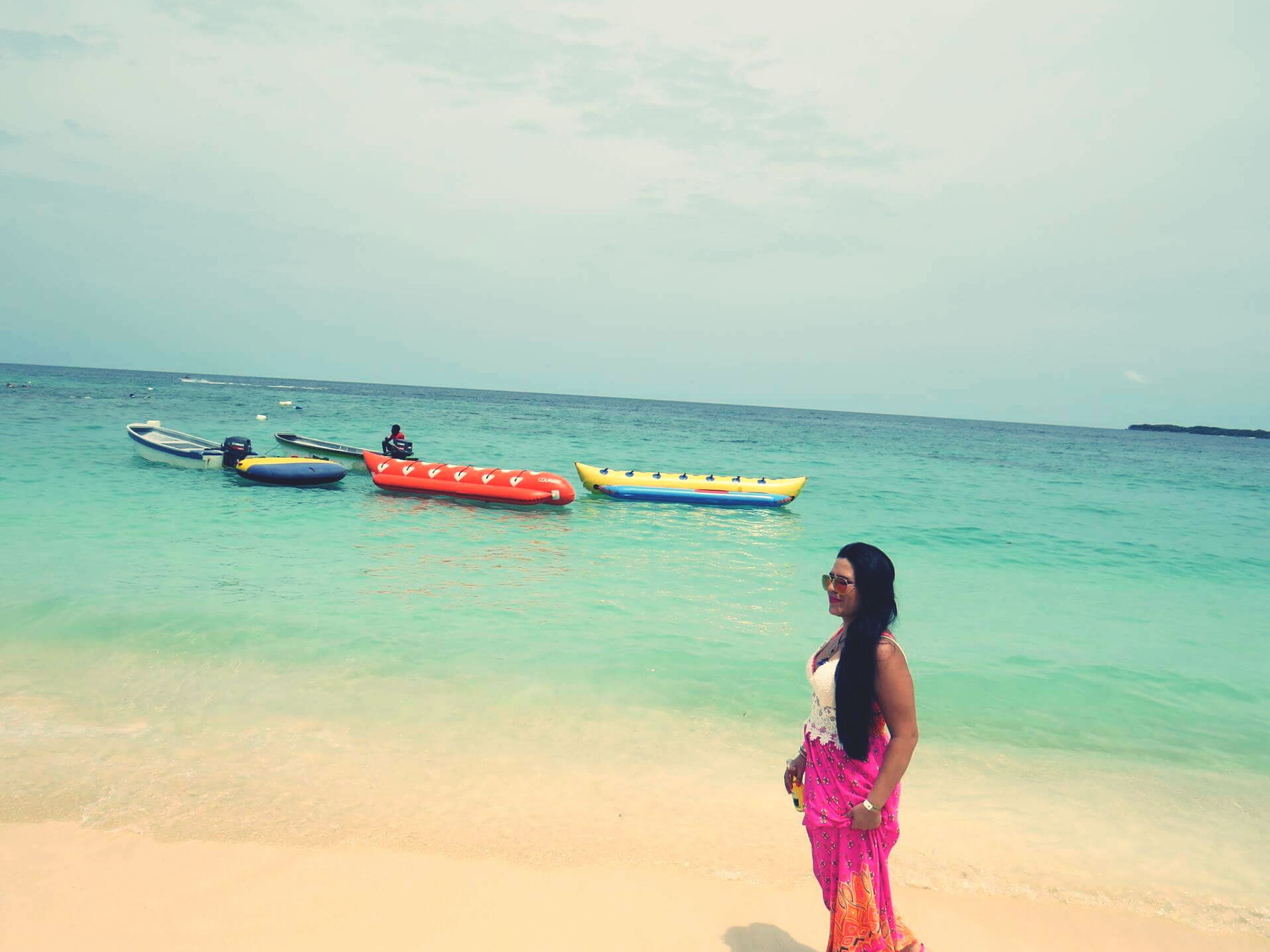 sea, horizon over water, beach, water, leisure activity, shore, nautical vessel, lifestyles, sand, transportation, casual clothing, standing, scenics, boat, three quarter length, tranquil scene, sky, beauty in nature, person, vacations, nature, wave, tranquility, non-urban scene, enjoyment, day, young adult