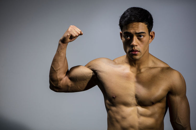 The muscular physique of a male fitness model put on display. The model displays his bicep muscle. Adult Asian  Athletic Body & Fitness Front Facing Human Body Man Nam Vo Shirtless Vietnamese Bicep Biceps Clenched Fist Fit Fitness Model Flexing Muscles Grey Background Handsome Looking Away From Camera Model Muscles Pectoral Strong Toned Torso