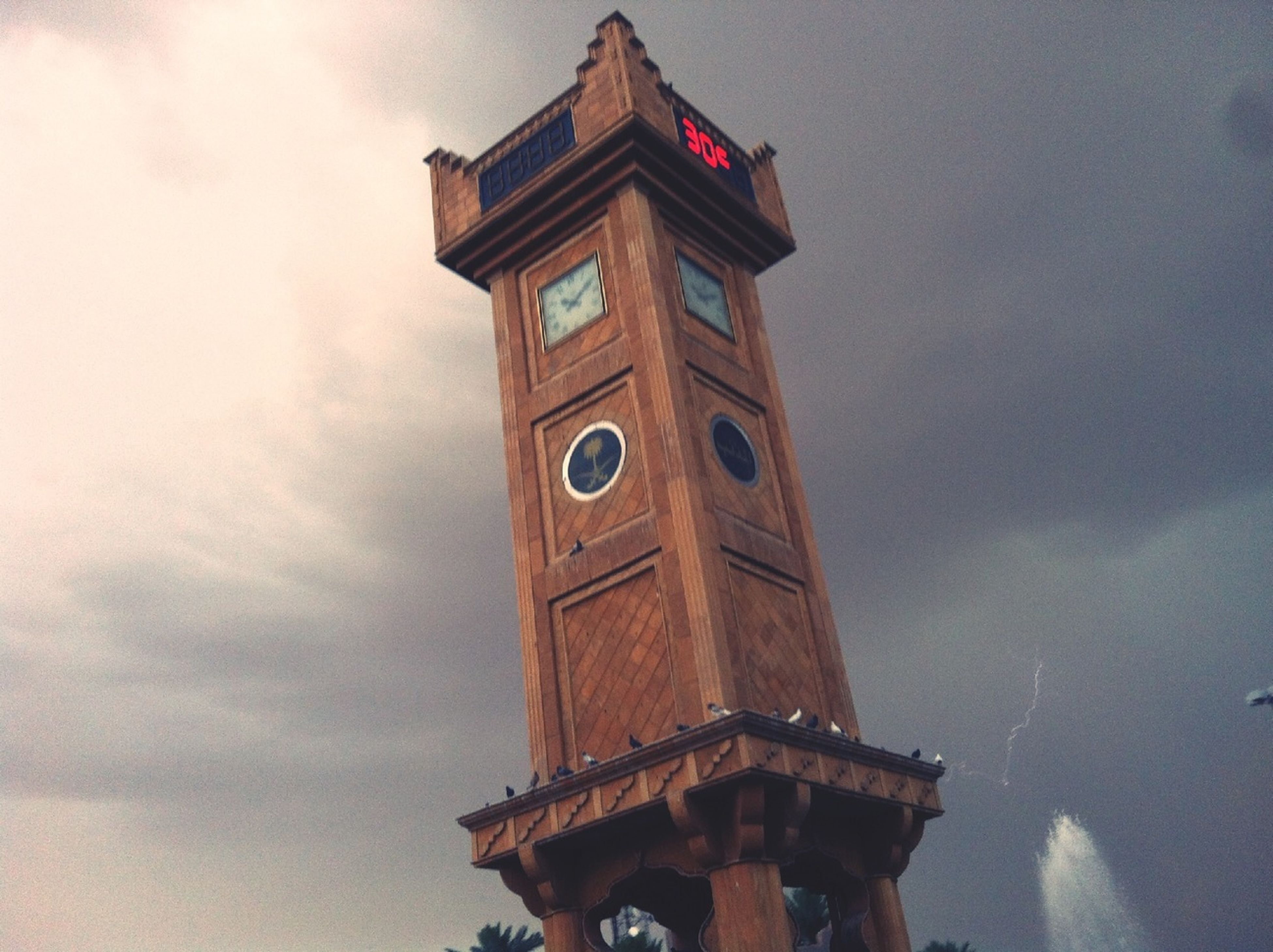 architecture, low angle view, built structure, building exterior, clock tower, tower, sky, clock, time, cloud - sky, tall - high, history, outdoors, no people, city, cloud, day, travel destinations, cloudy, religion